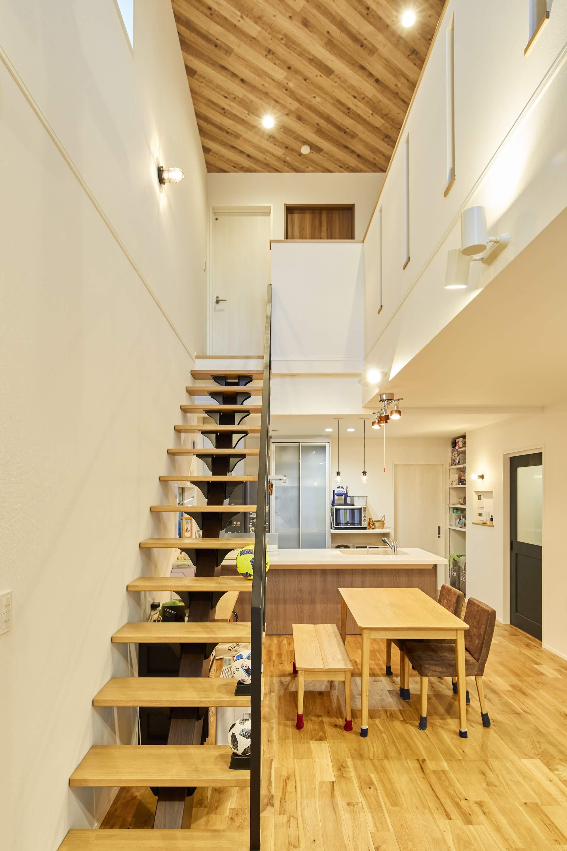 大きな吹抜けにはリビング階段も設置。無垢の床材とブラックのアイアン手すりの調和がポイント