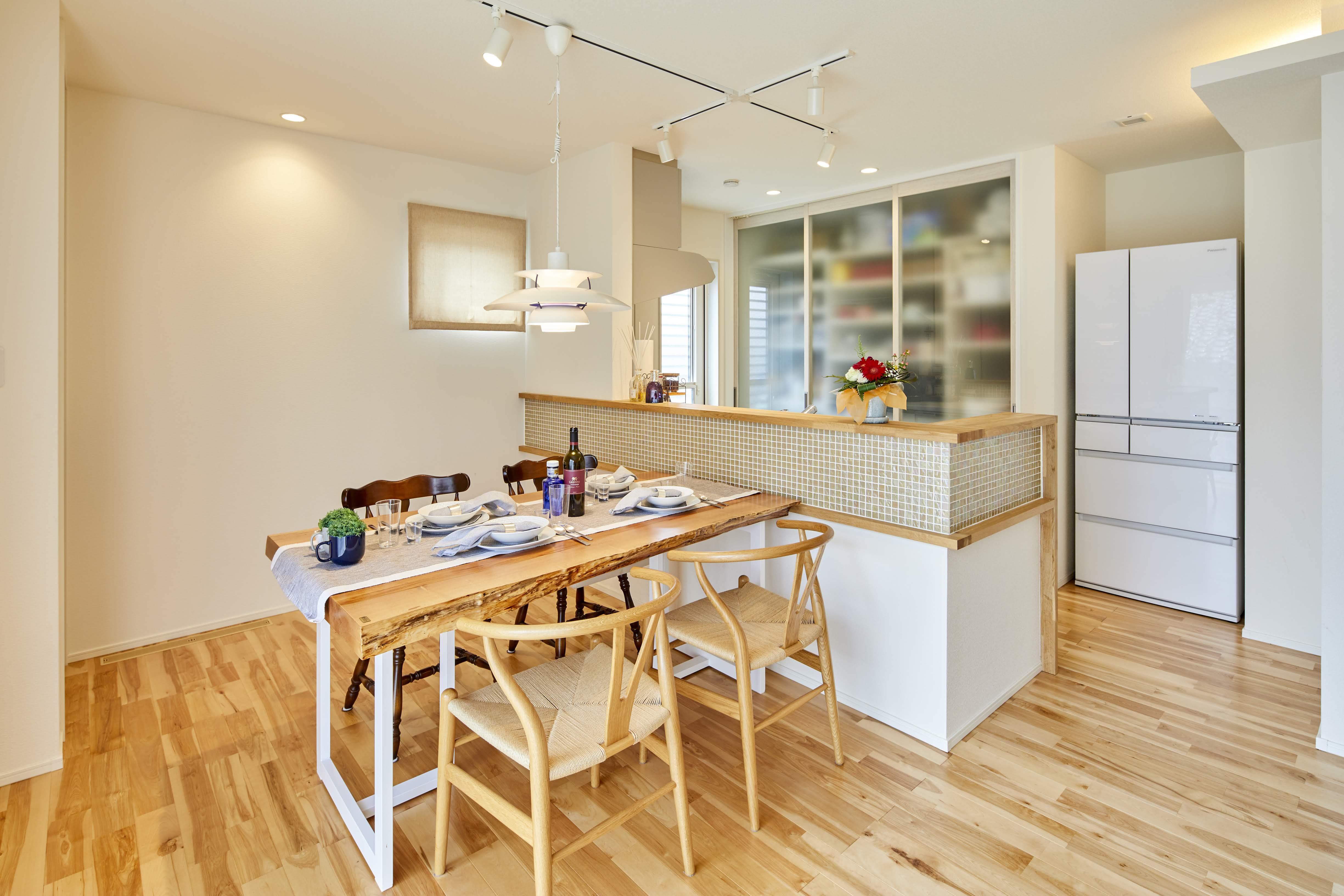 キッチンの背面収納にはスケルトンの収納扉を採用。 大容量の収納をスッキリとした印象で実現した