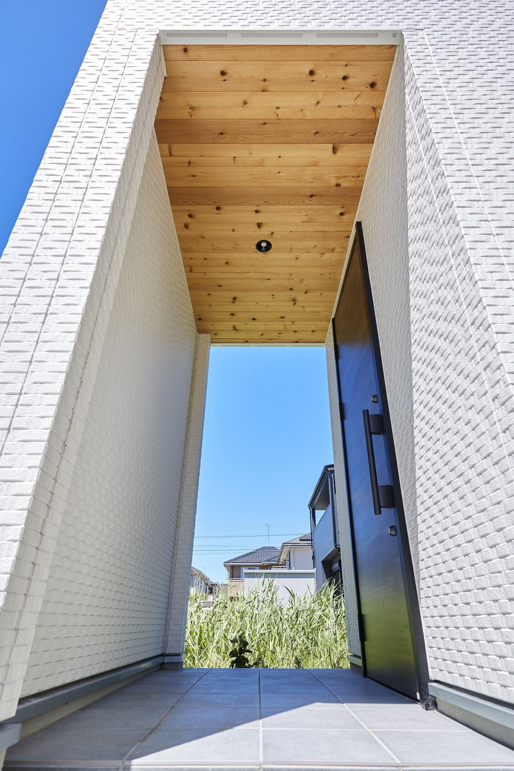 玄関ポーチはホワイトを基調とし、 天井には木材パネルをあしらった