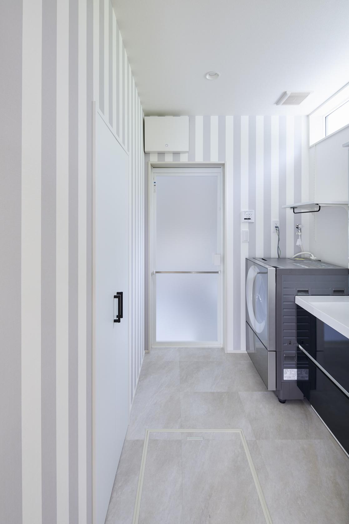高い位置にある窓から光が入り、 明るく清潔感ある洗面室に。ストライプのアクセントクロスも可愛らしい