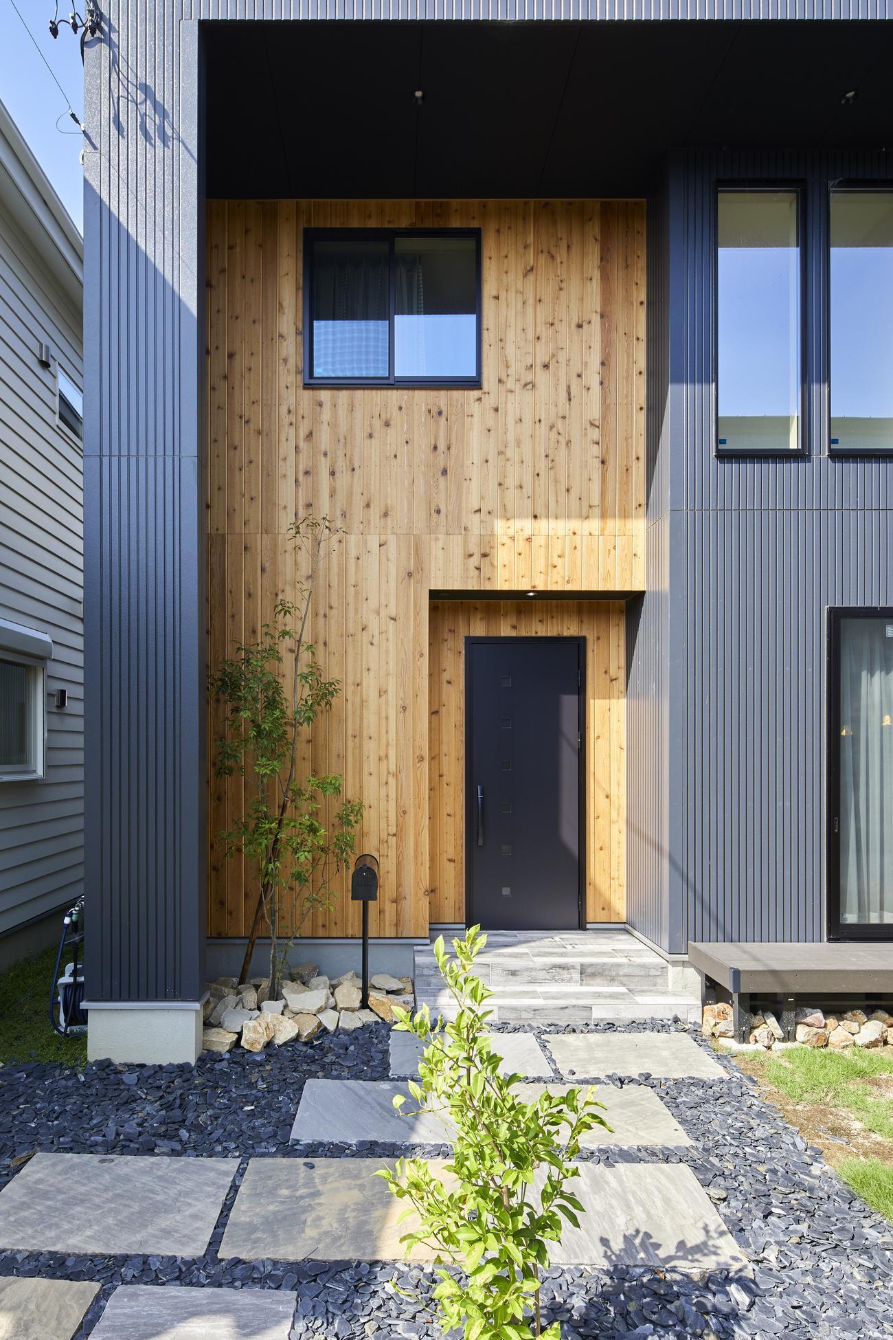 石貼りのアプローチと 天然木の外壁が美しい