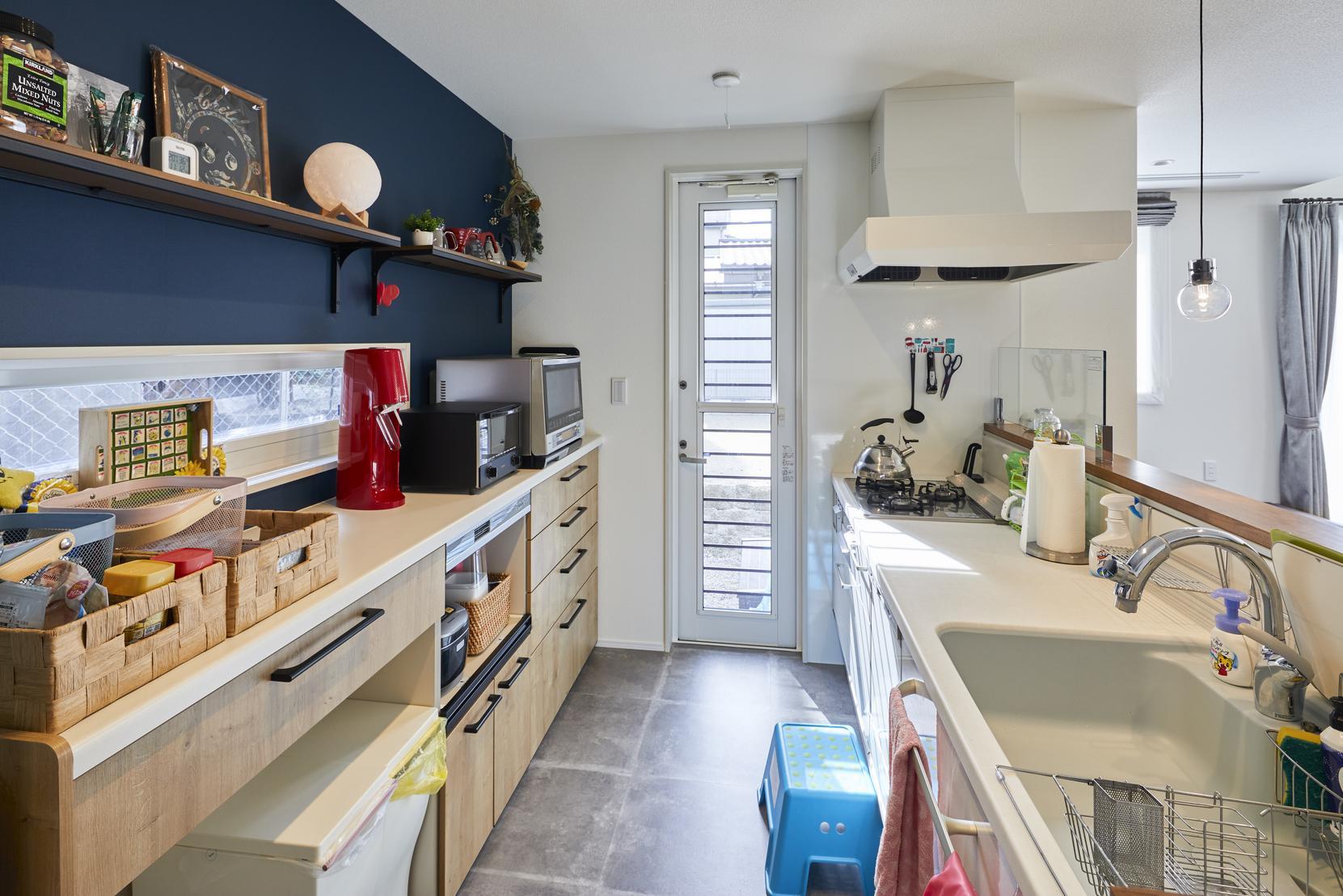 キッチンの背面収納は低めに設計し、開放的に。上部の造作棚にはお気に入りの小物を飾れる
