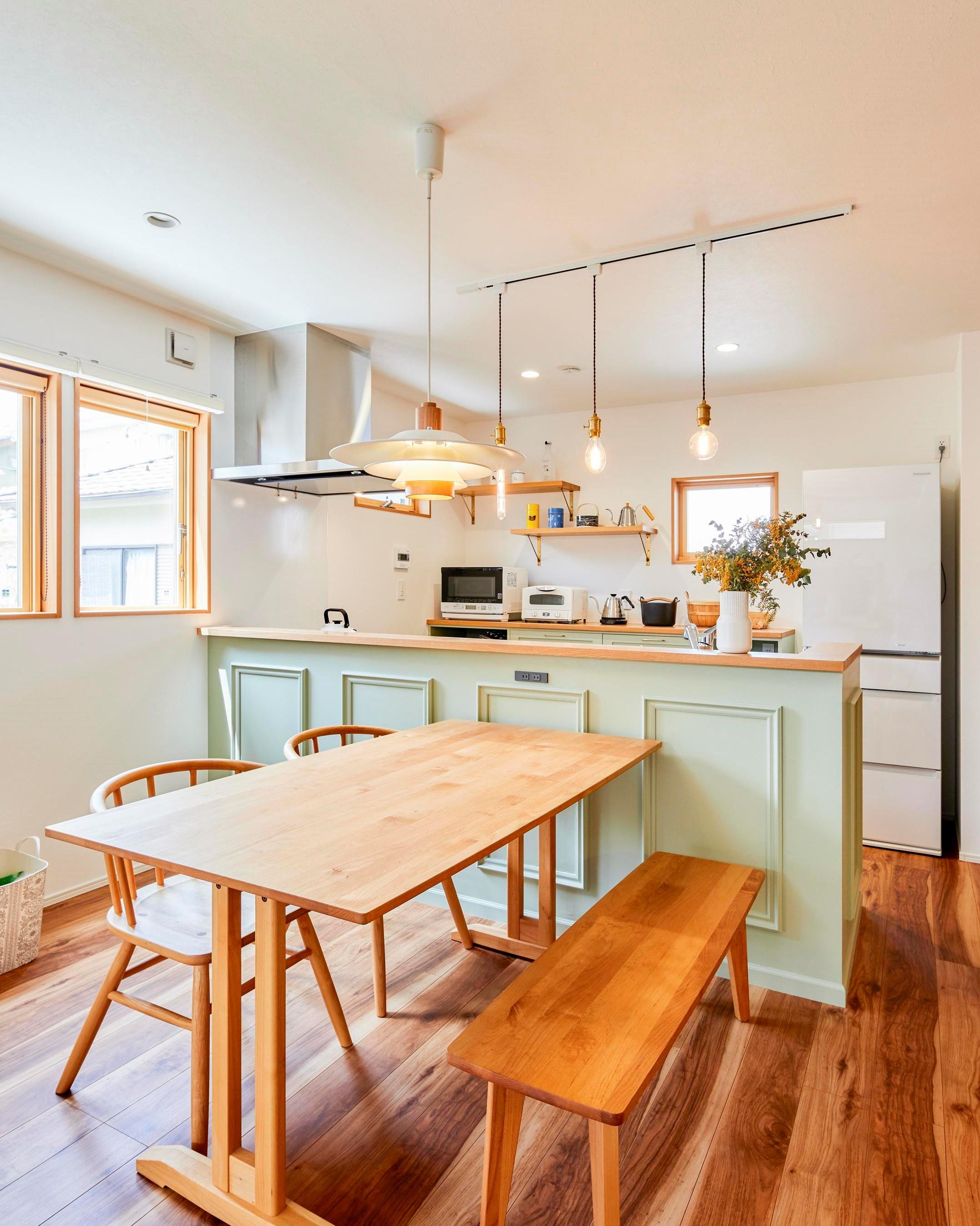 キッチンはカップボードと腰壁を可愛らしい色使いで造作し、空間との調和を生み出している