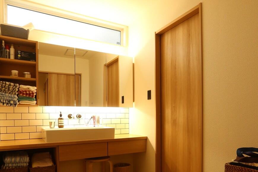 こだわりのオリジナル洗面台を造作。カフェ風のデザインと間接照明で柔らかい印象を与えている
