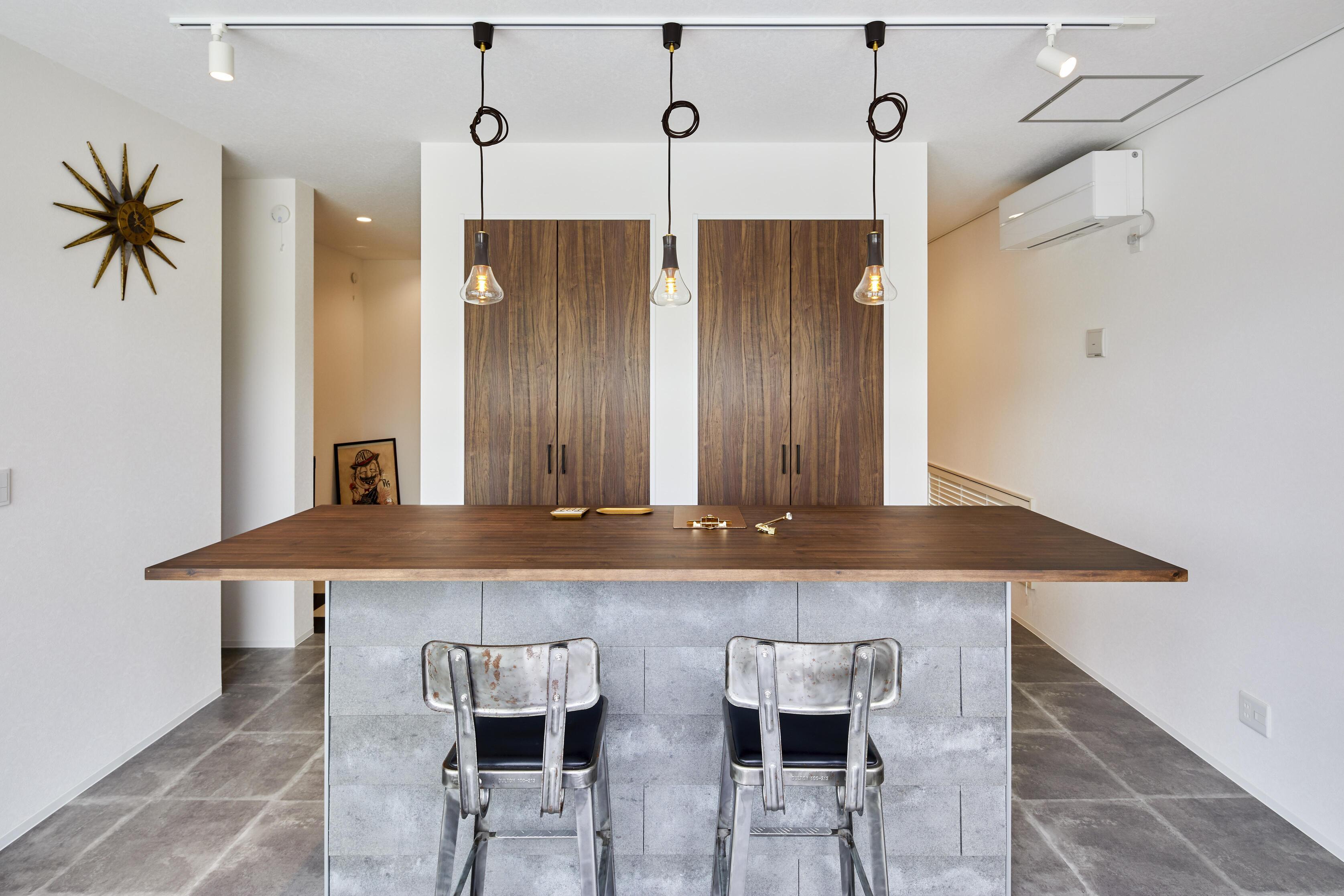 美容室側の受付スペース。濃いめの木目とセメント系の床と、異素材を上手く組み合わせた