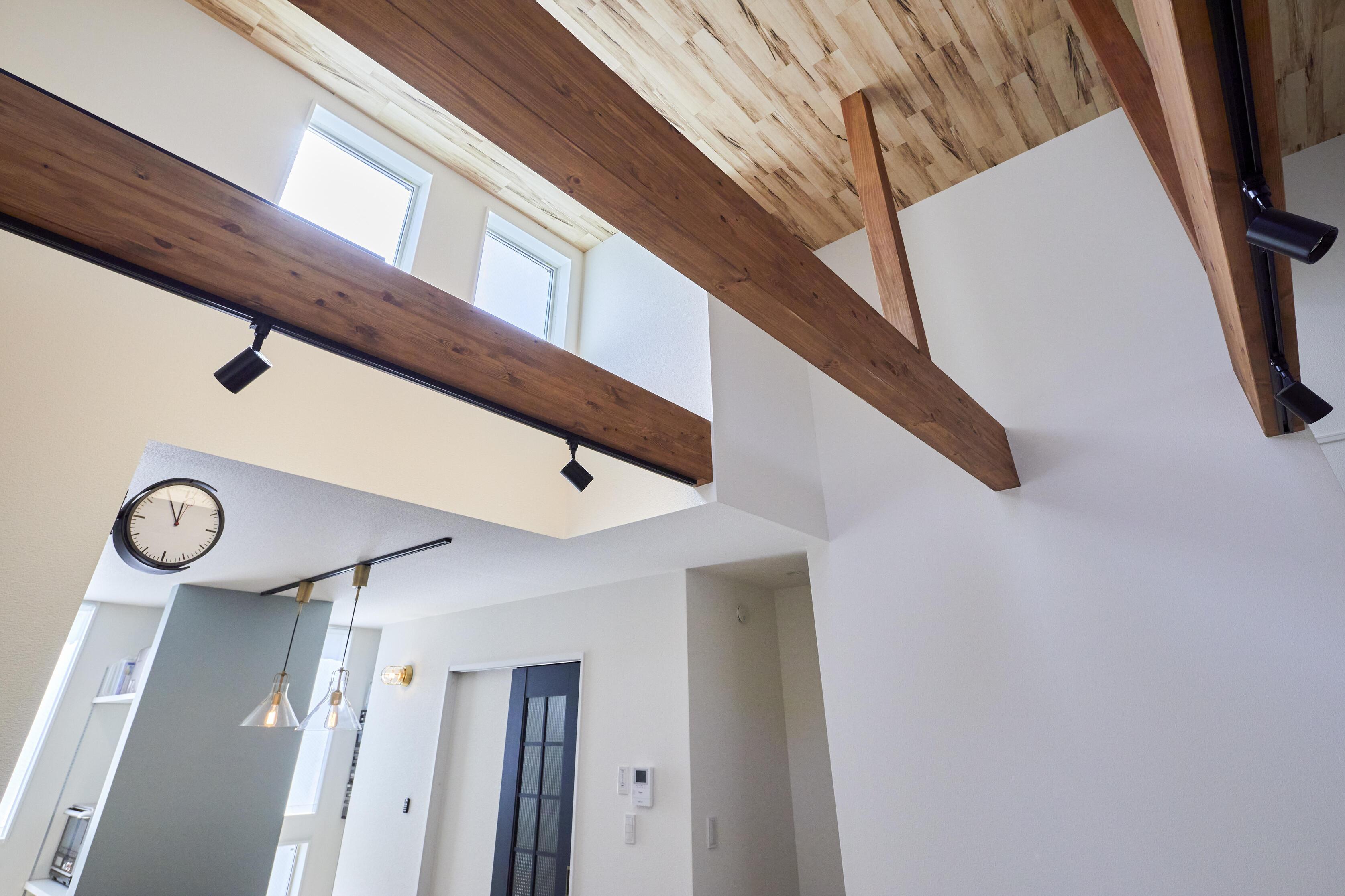 大きな吹抜けの天井には木調クロスをあしらった
