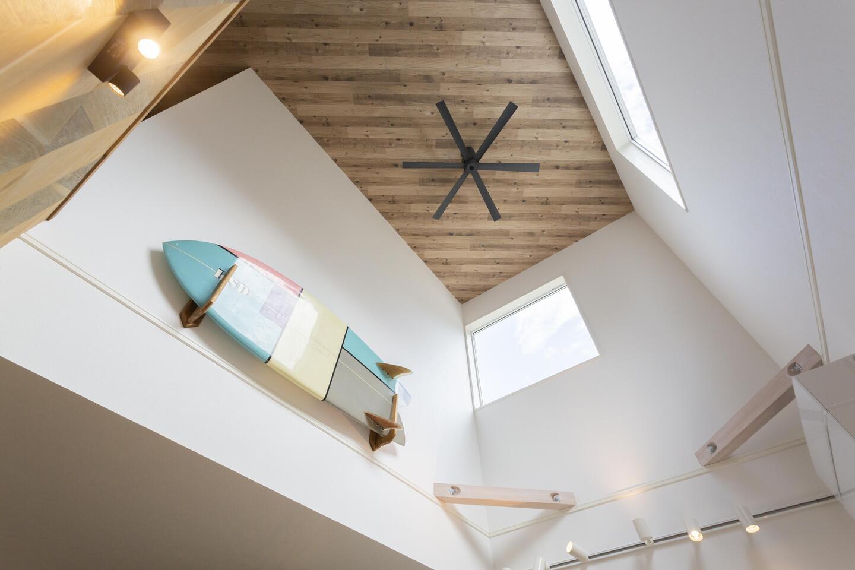 大きな吹抜けの天井には木調アクセントクロスを採用して更にオシャレに。サーフボードがマリンテイストを強調している。