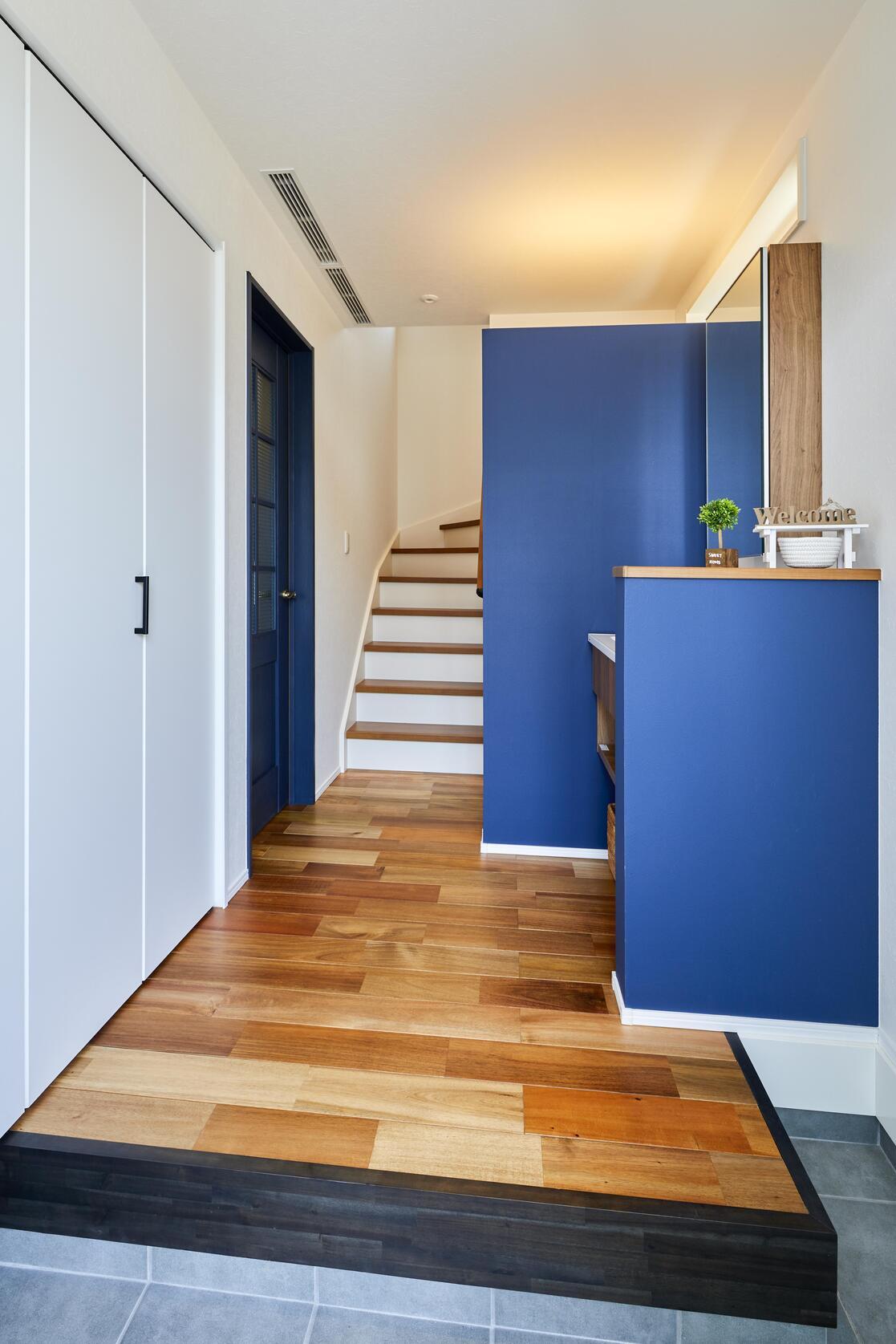 ネイビーをアクセントとした玄関。幅の広いアカシアの無垢材が美しい