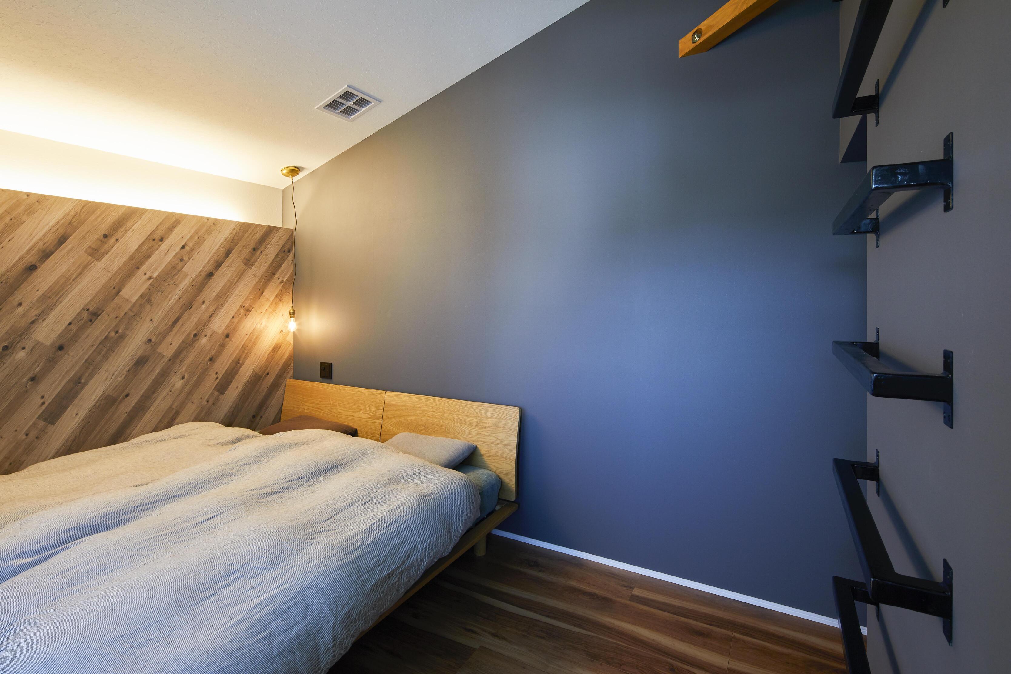 勾配天井でロフトのある寝室。ダークトーンでまとめ、間接照明で落ち着きのある空間に
