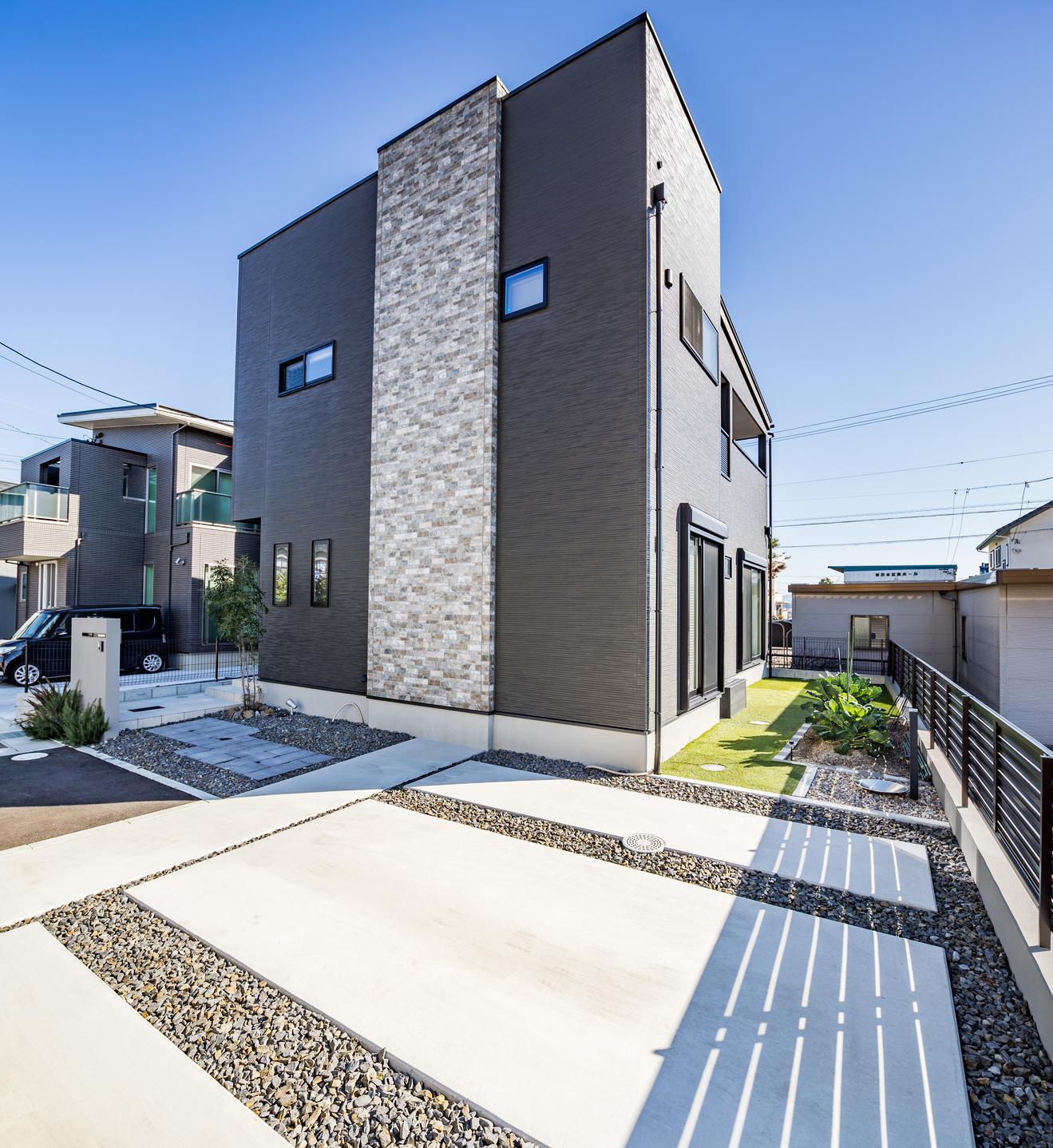 シンプルながら石調のアクセントを施しており、建物が引き立つ外構で上質な存在感を放つ