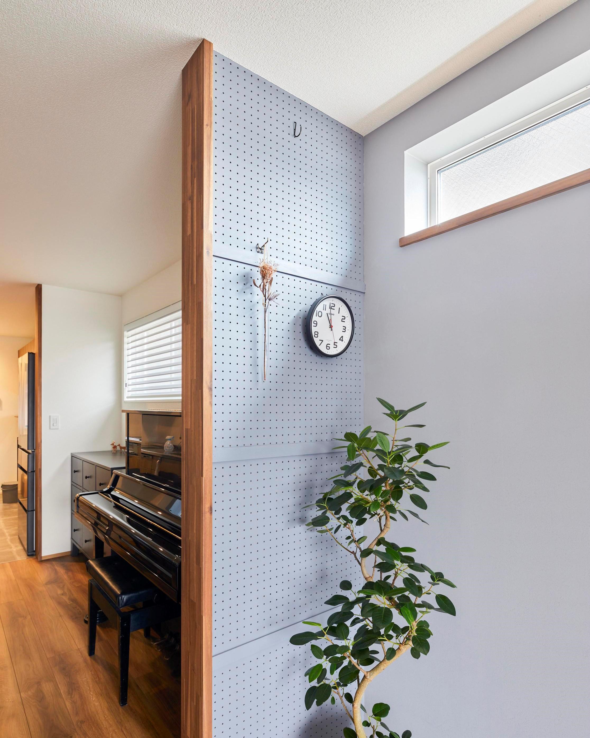 LDKの壁の一部は有孔ボードにし、お気に入りの小物や時計を飾ることができる