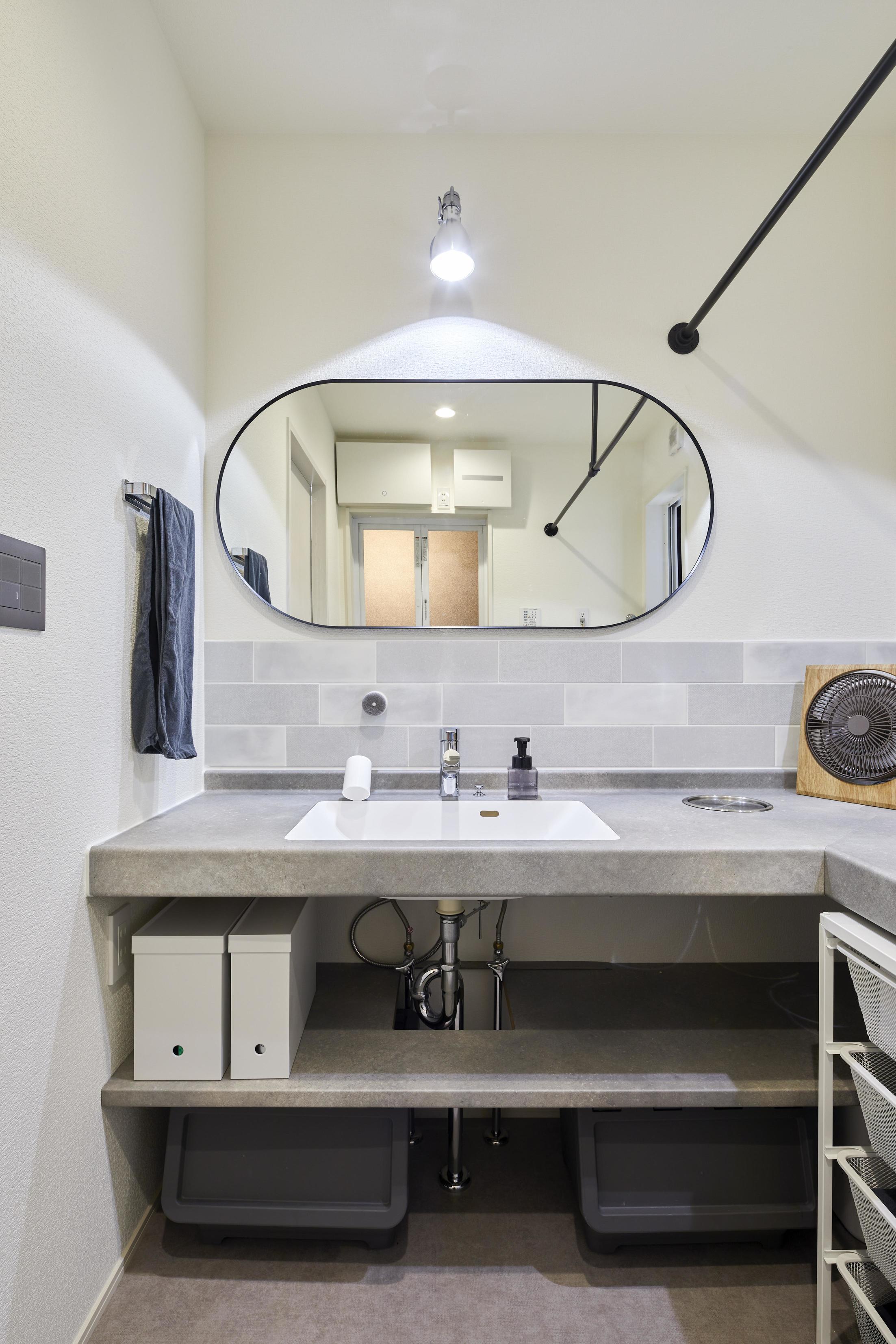 楕円型の鏡が可愛らしい洗面所。室内干しできるようにハンガーパイプも設置している