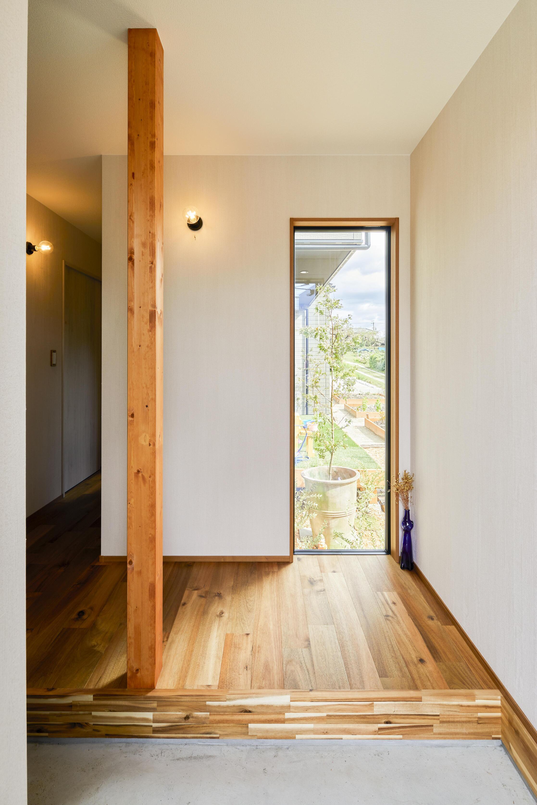 玄関から入るとまず目に入るのが正面の窓。まるで額縁のように庭の風景を切り取り、季節の移ろいを感じさせてくれる