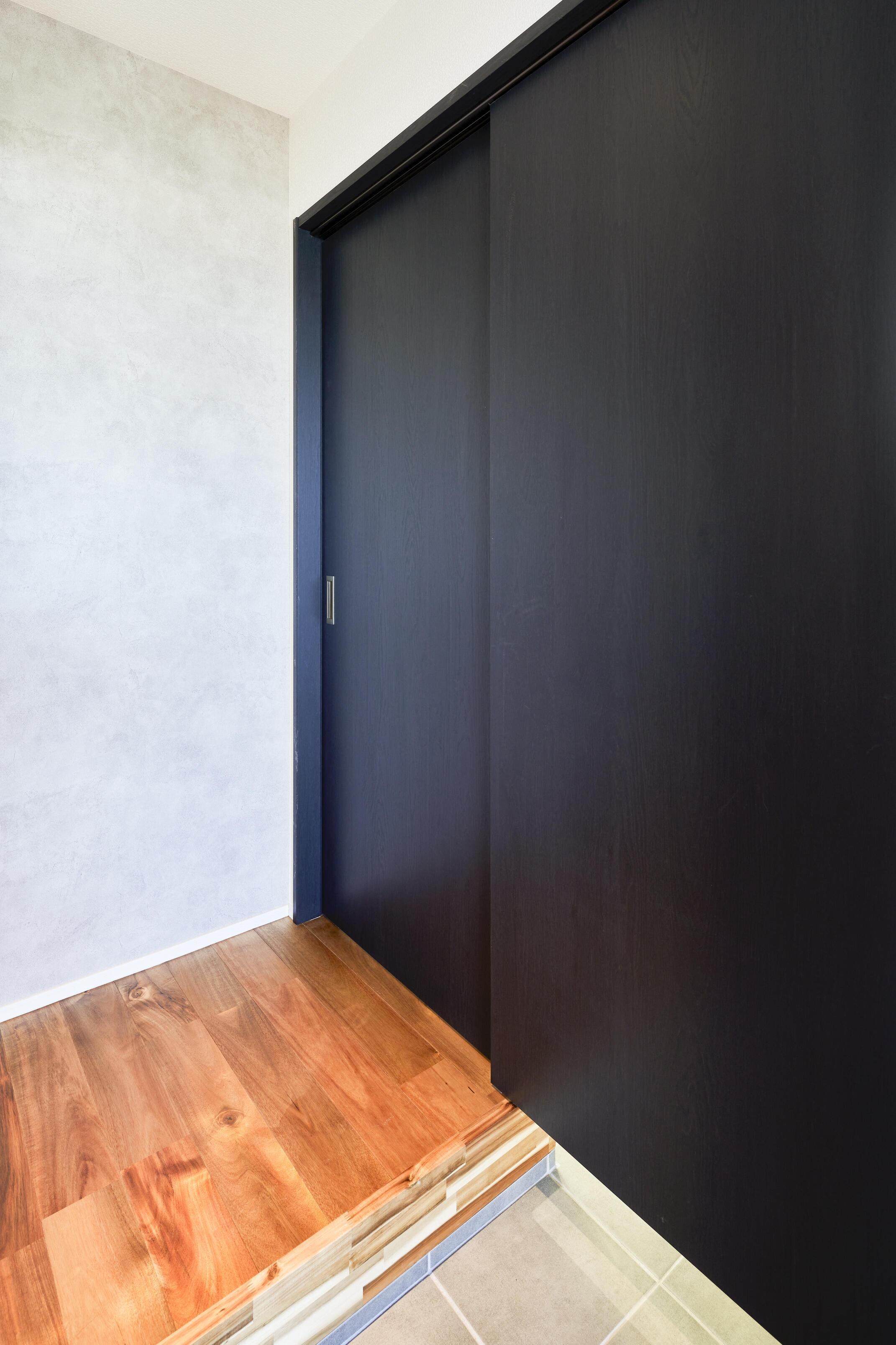 玄関正面にモルタル調のアクセントクロスにネイビーの建具で落ち着いた大人っぽい空間に