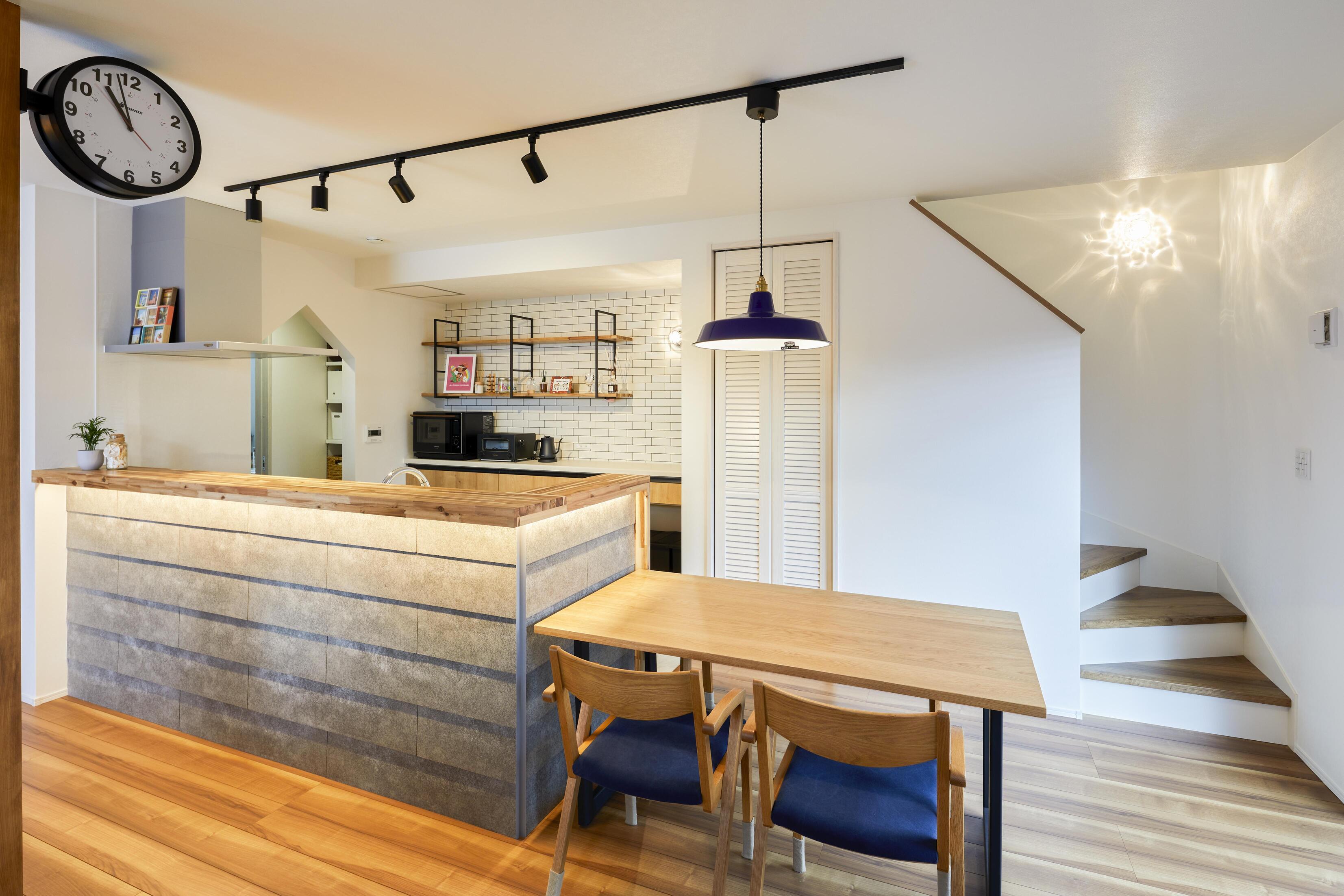 キッチンの笠木には間接照明を仕込み、セメントの質感を生かした腰壁を引き立てる