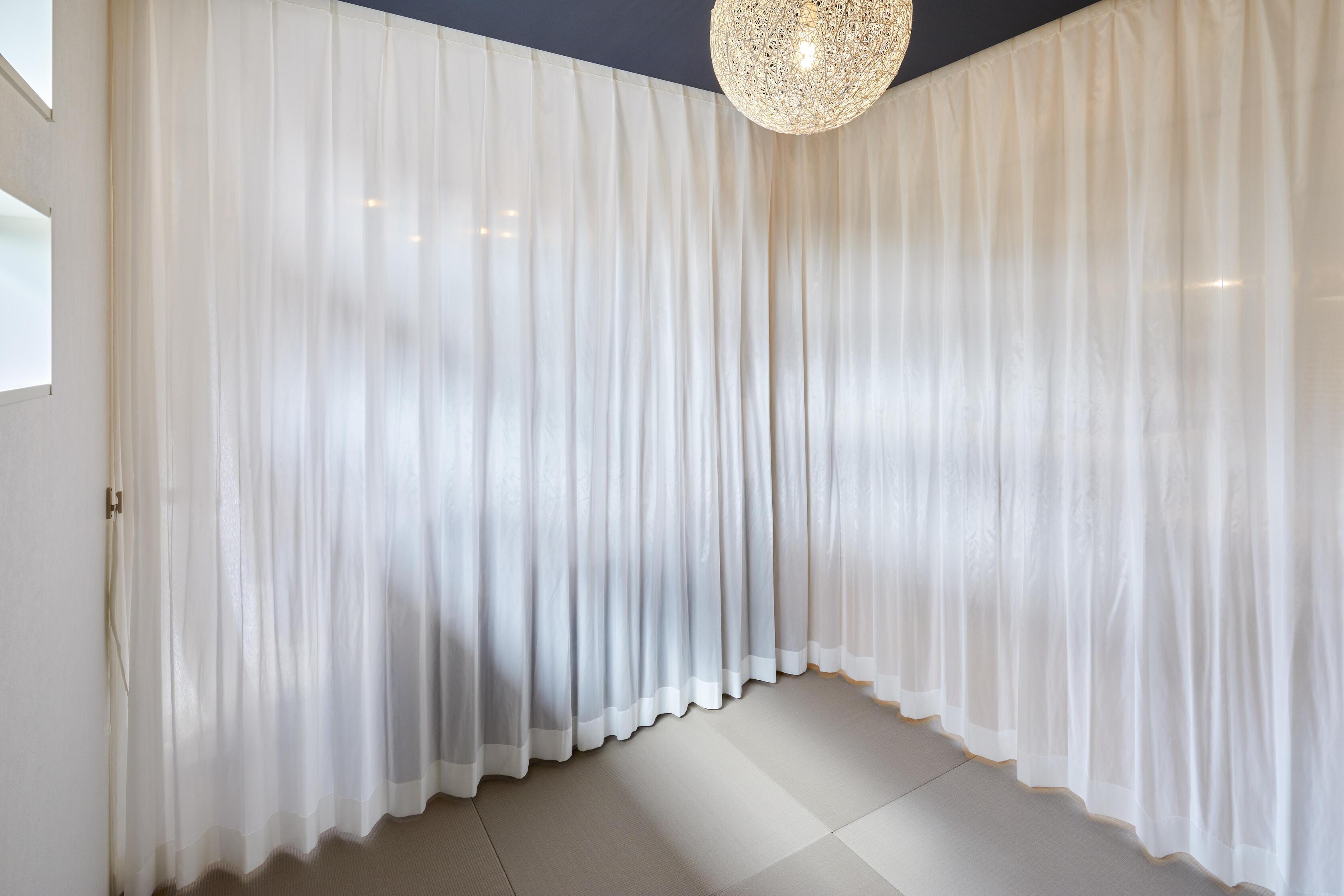 空間と分けたい時は、天井に取り付けたウェーブ論カーテンで仕切ることも可能