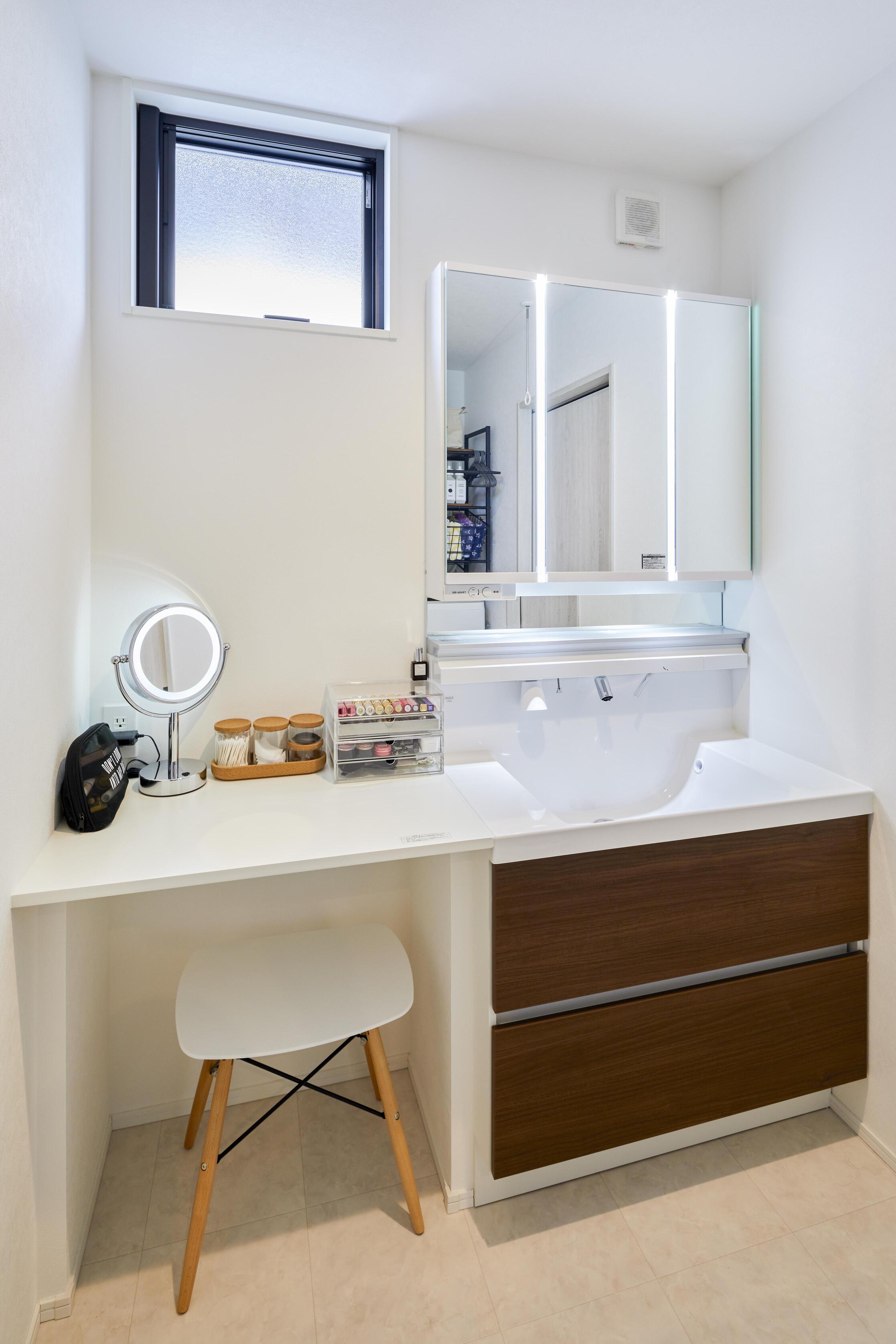 洗面化粧台の横にはカウンターデスクを造作。アイロンをかけたりメイクをしたりと使い方は様々