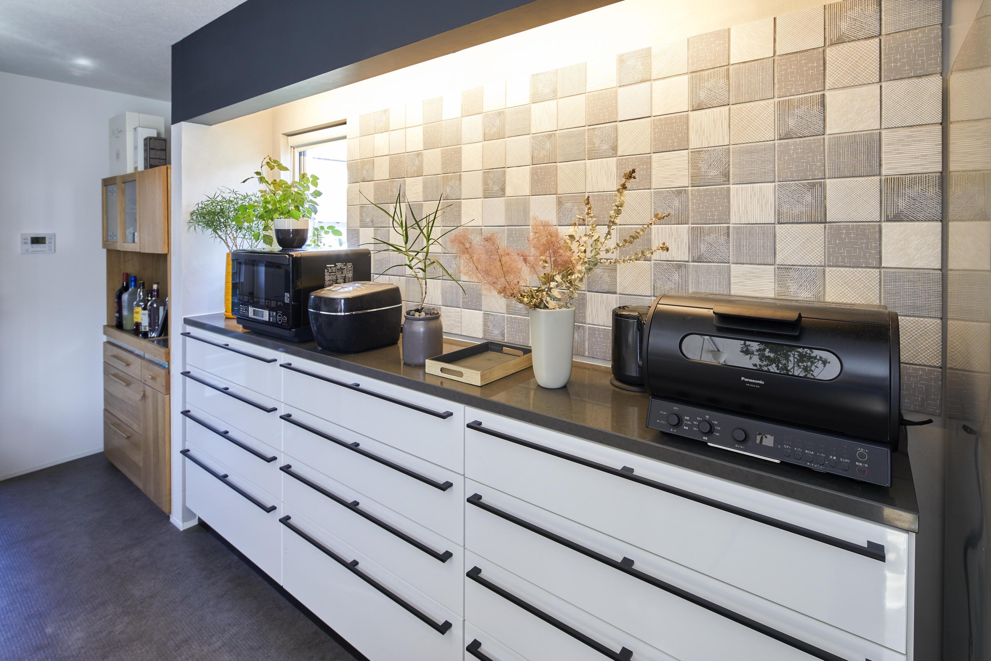 キッチンの背面にはインガセンぺのモダンタイルと間接照明をあしらいシックな仕上がりに。キッチンの奥にはパントリーも設計している