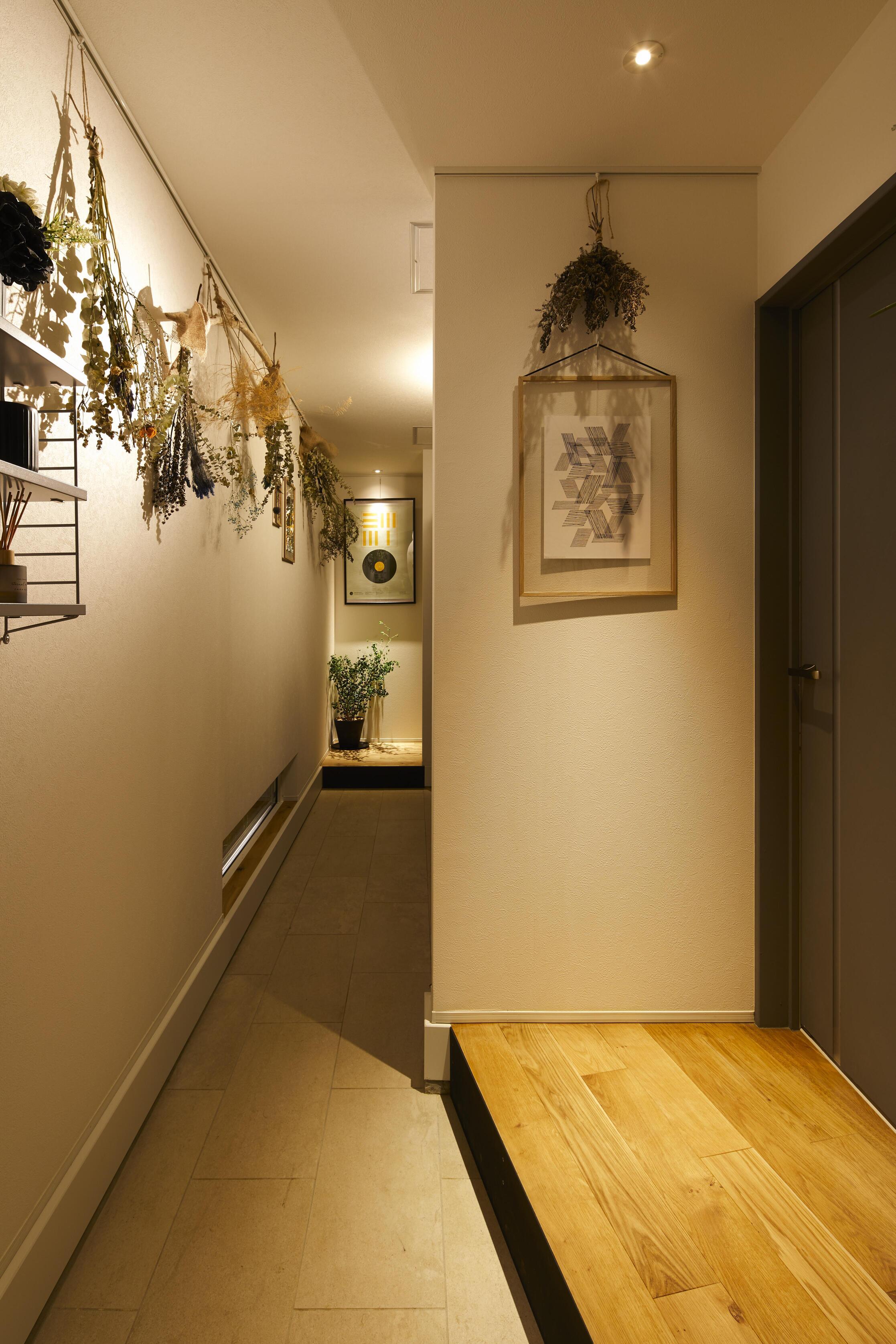 長い土間スペースを持つ玄関。ゲスト用と家族用のリビングドアを分けており、家族はシューズクローセットを横切り入室する間取り