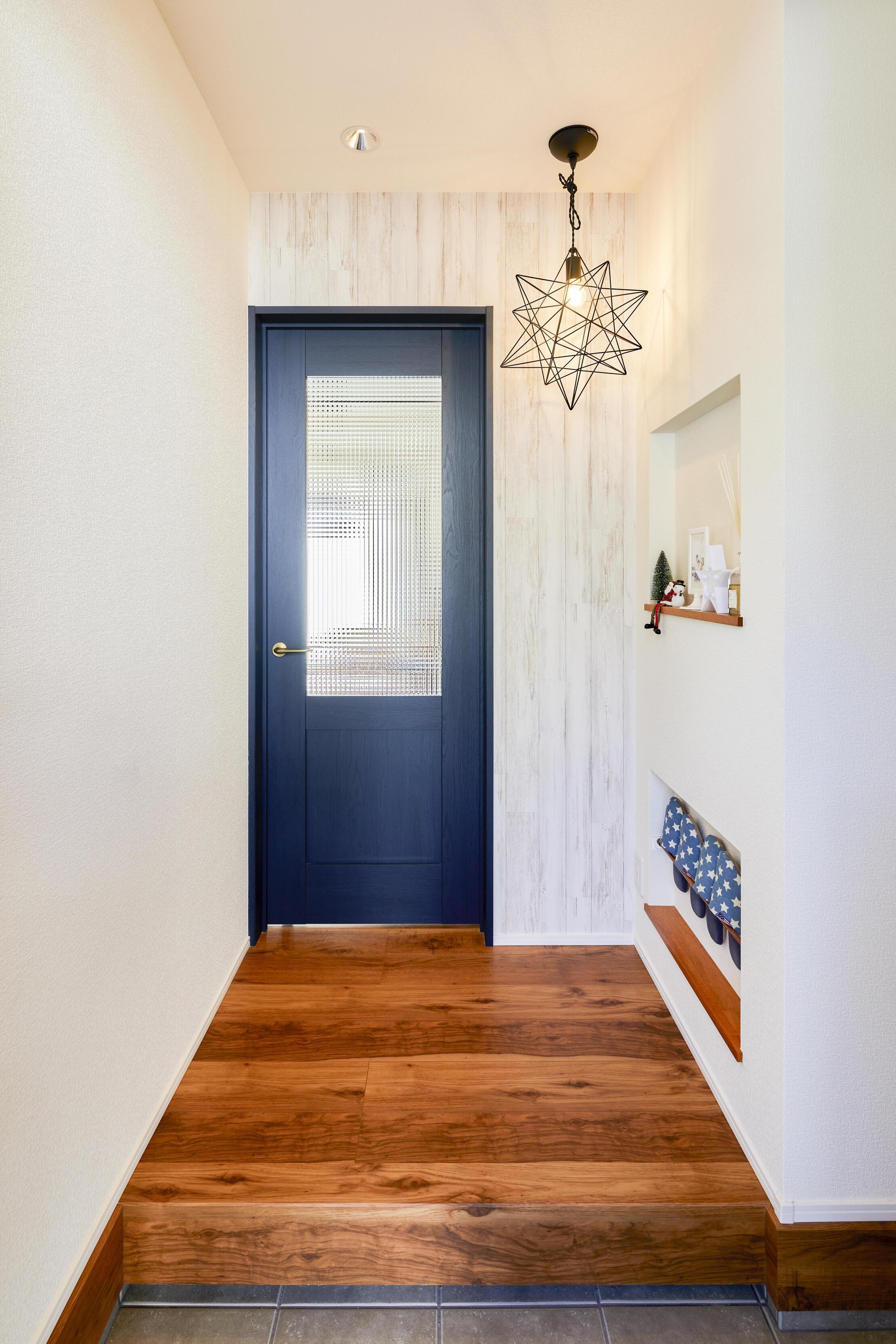 框組デザインのドアと、印象的なフレームのペンダント照明が素敵に出迎えてくれる玄関。スリッパを収納できるニッチも便利