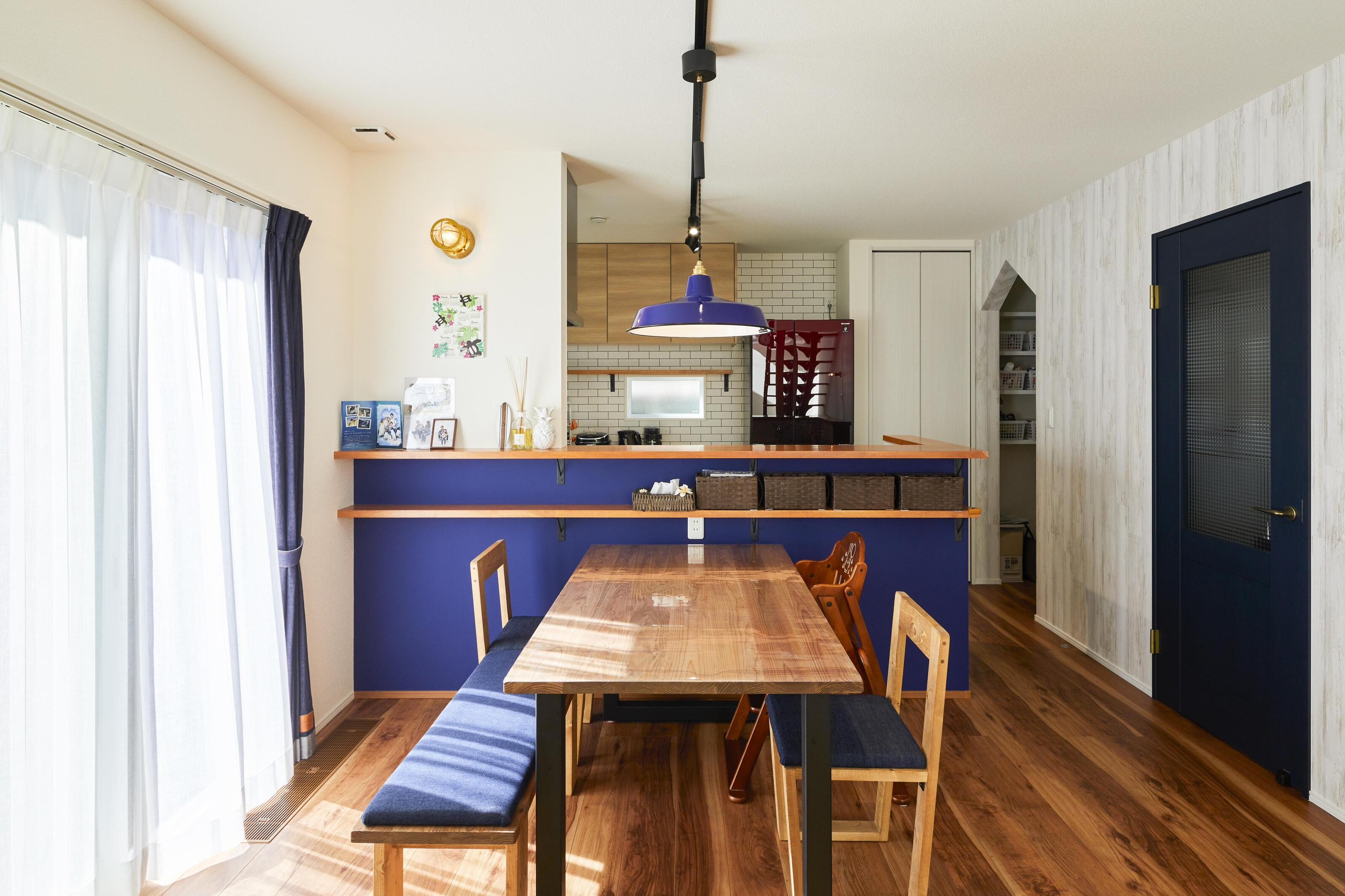 ネイビーをアクセントに取り入れたキッチン。棚も取り付けちょっとした小物を置くのに便利