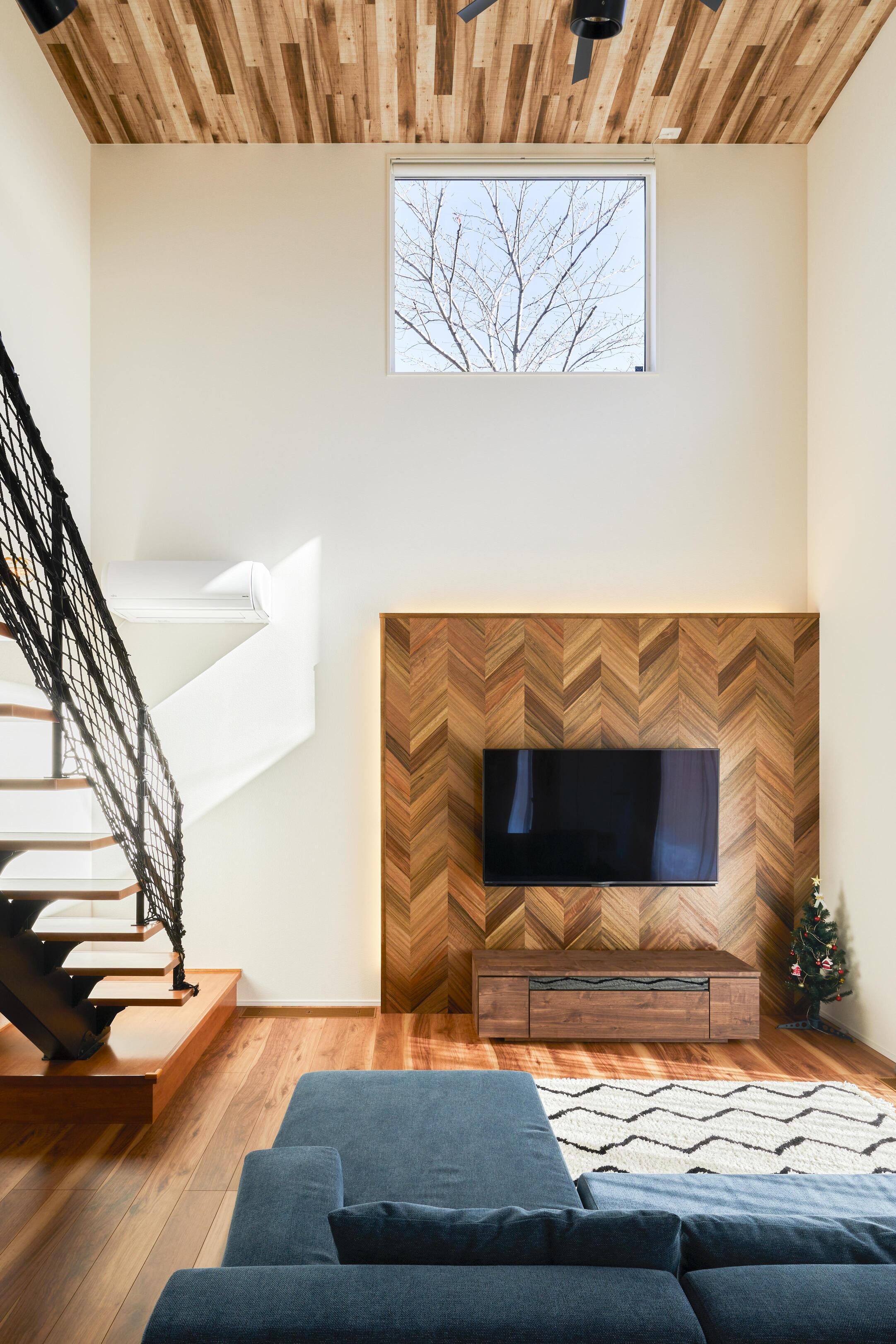 吹抜けの上部には大きな窓を設置。木々の風景を絵画のように切り取り、季節の移ろいを感じさせてくれる