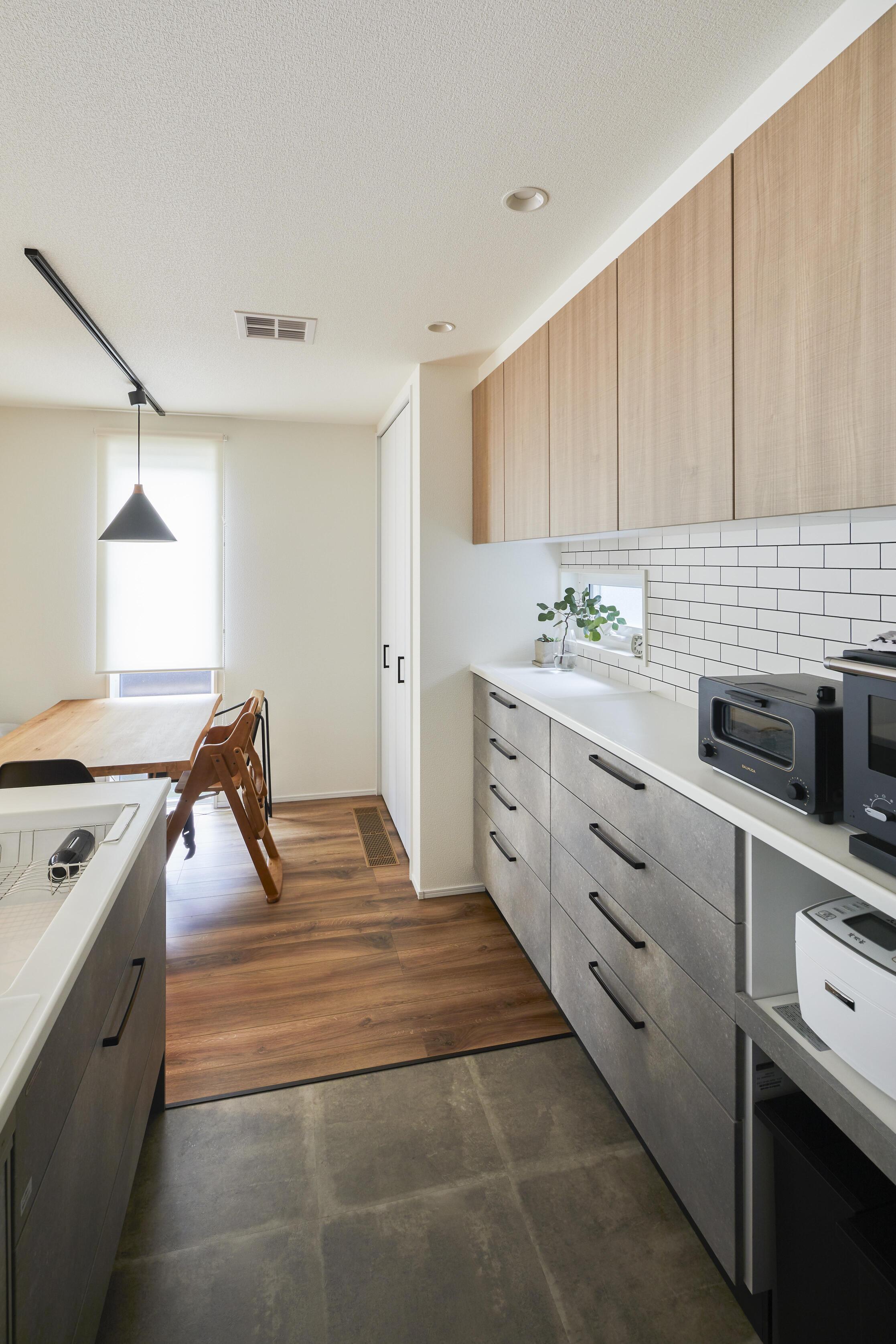 対面型のキッチンを採用。面材をコンクリート風に仕上げ、リビングのTVボード背面クロスと風合いを揃えた