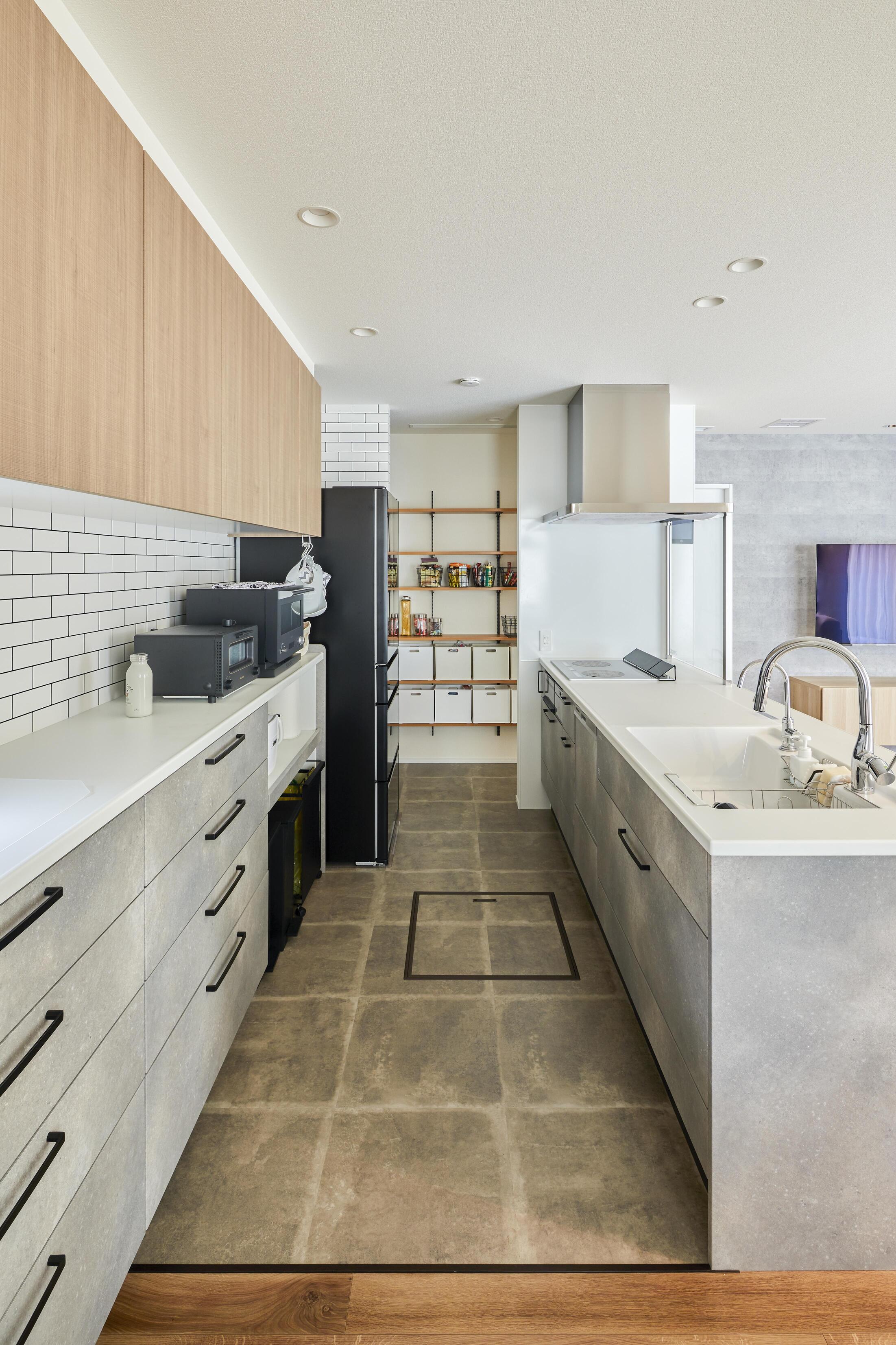 コンクリート調、タイル調、木質調を絶妙なバランスで織り交ぜたキッチンに。奥にはパントリーが設計されている