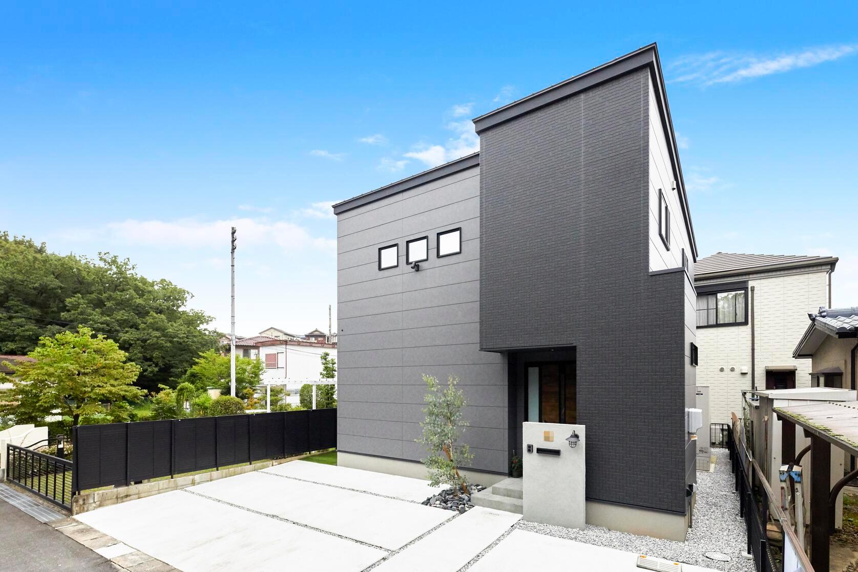 グレーとブラックを組み合わせたかっこいい外観。玄関ドアを木目調にすることでクールすぎないようにコーディネートした