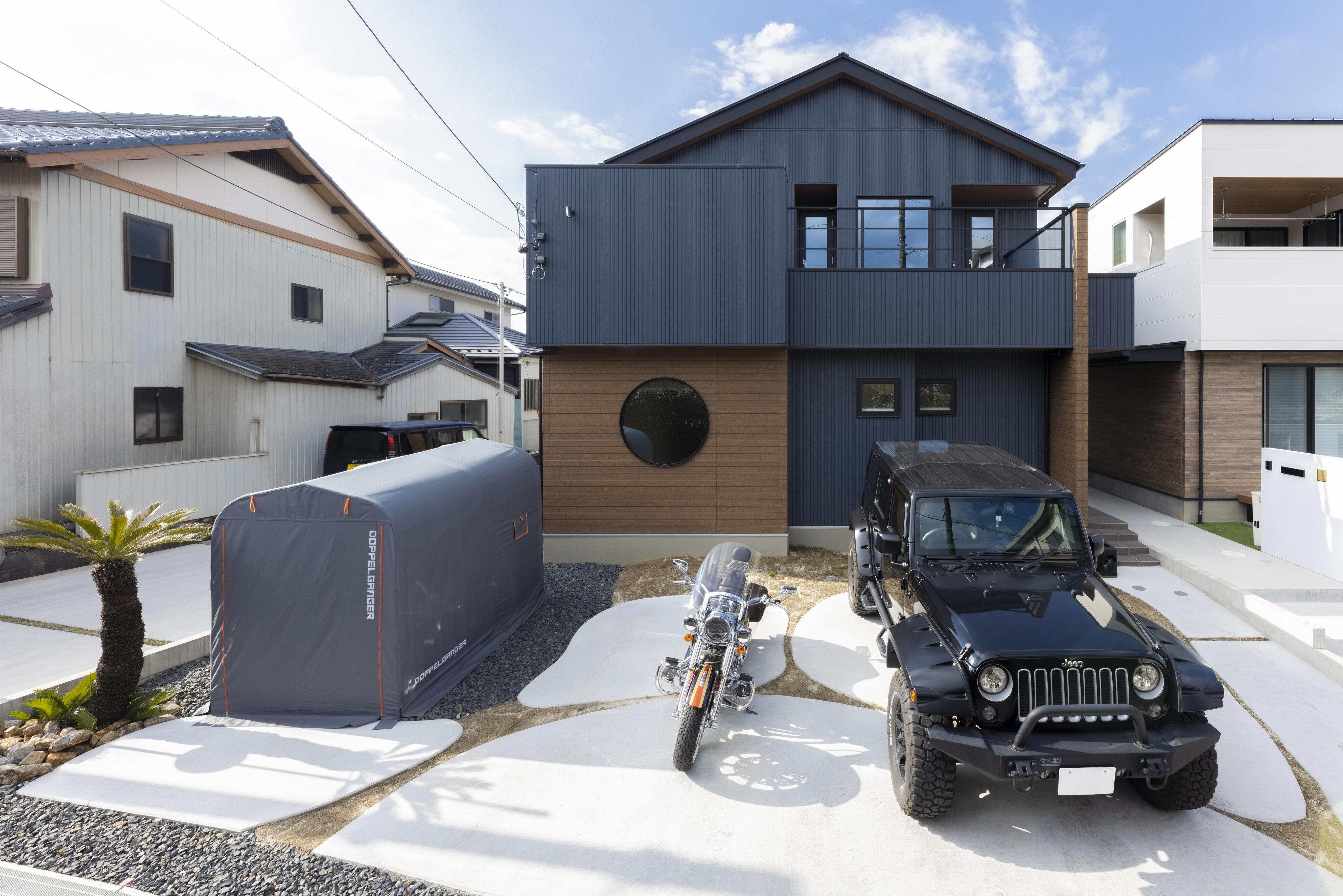 楕円を組み合わせたコンクリートでつくられた駐車スペースを持ち、活動的な印象を受ける外観