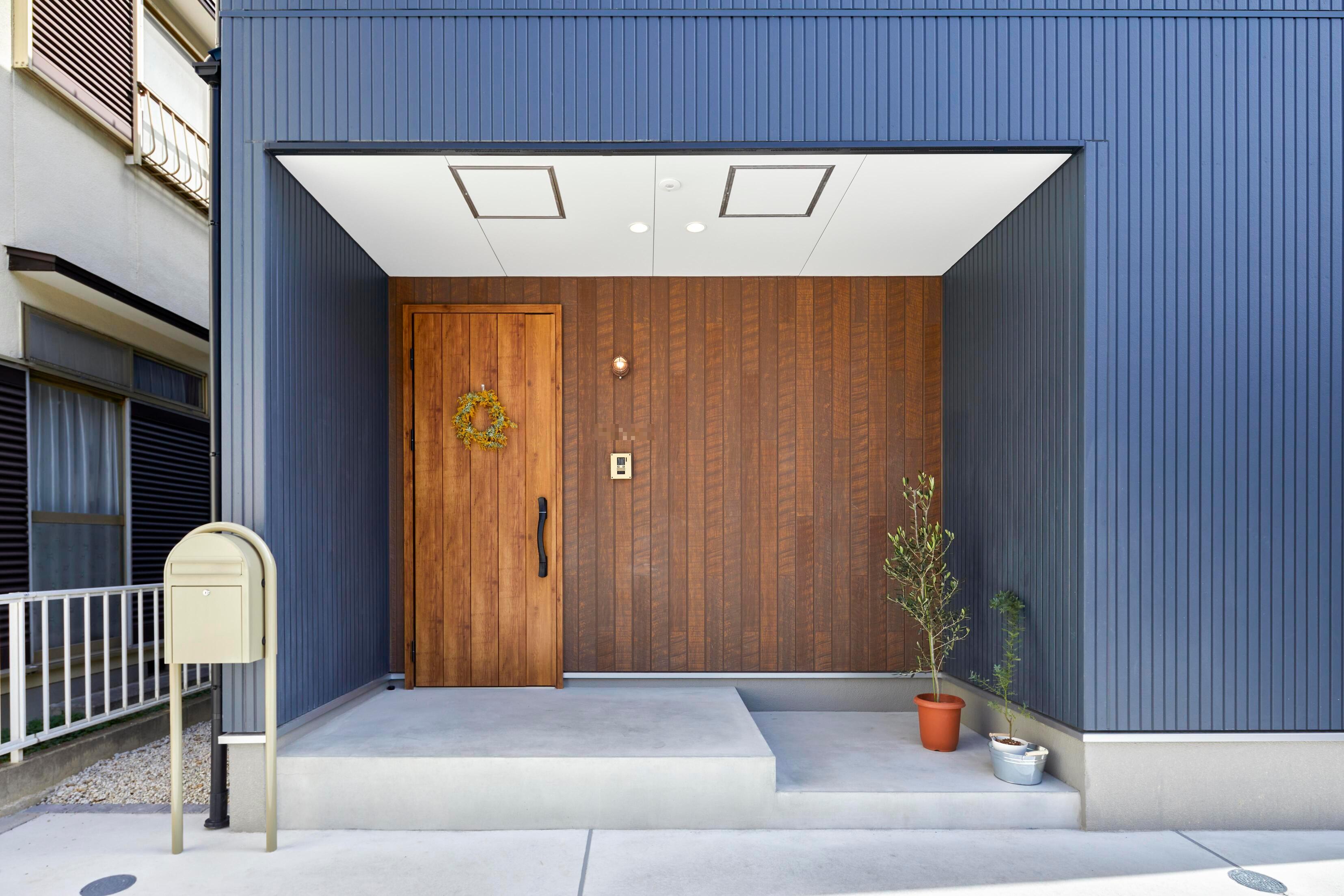 外壁はネイビー×木調サイディングでシンプルながら可愛らしい印象