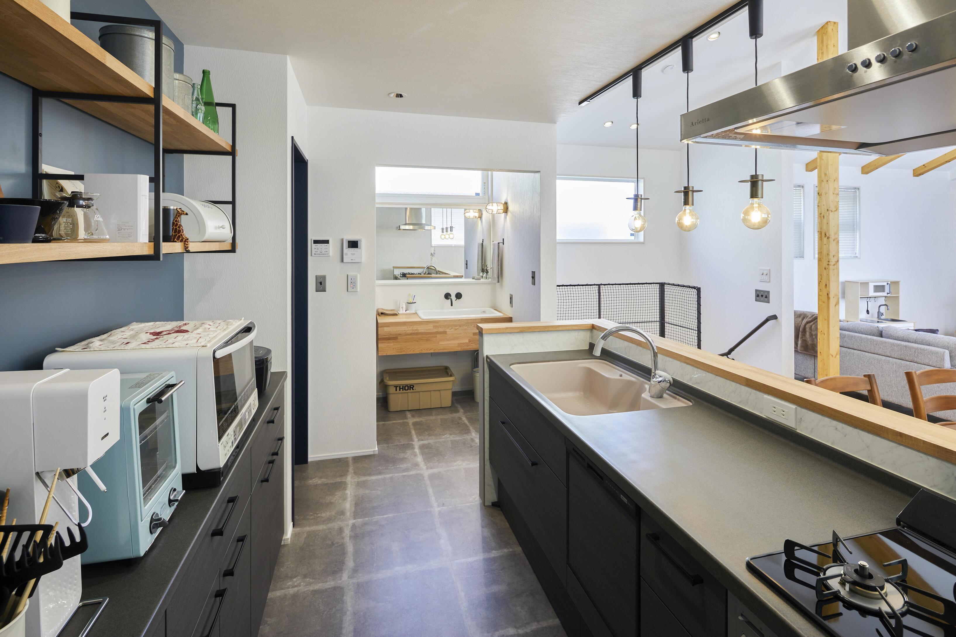 キッチンから洗面台までの水回りの床はコンクリート調にして、空間を緩やかに仕切っている