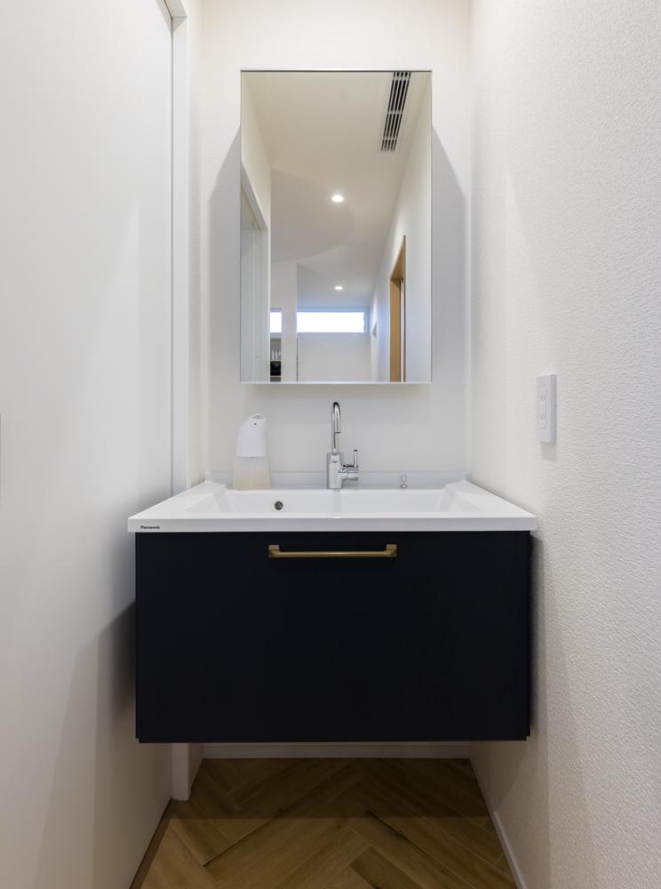 玄関ホールには、ネイビー×真鍮を使ったウェルカム洗面を設置。来客の方にも気兼ねなく使っていただける