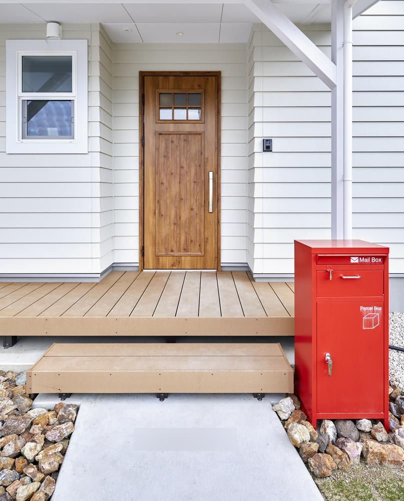 赤色のポストとパイン柄の玄関ドアが差し色の玄関は、カリフォルニアテイストの外観を引き立てる