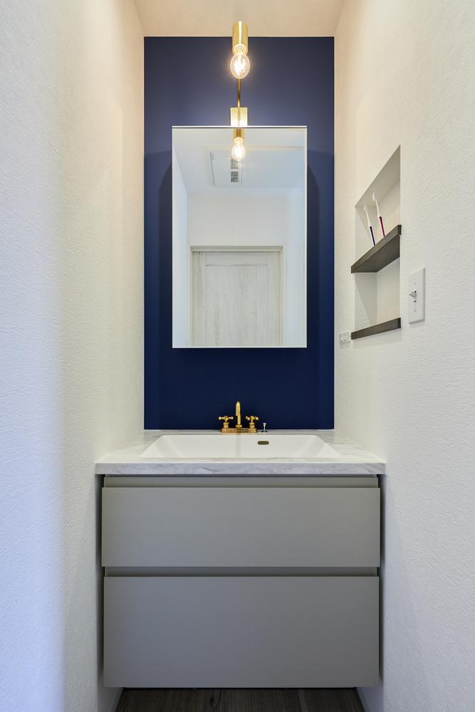 ゴールドの水栓・照明と大理石調の洗面ボウルでエレガントに決めた造作洗面台