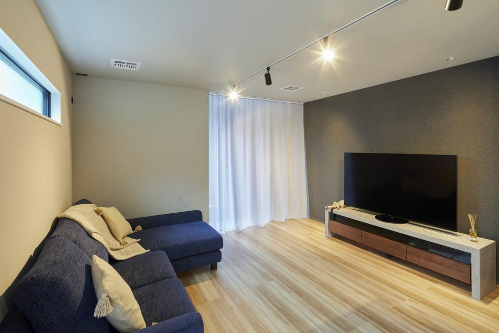 無機質な質感の家具と、柔らかな木目のフローリングが調和しシンプルで洗練された空間に