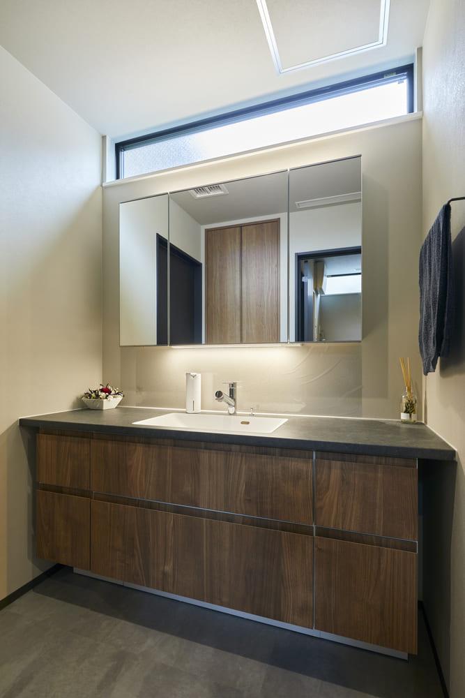 広々とした造作洗面台。鏡の上下に照明を設置し、ホテルのような印象に