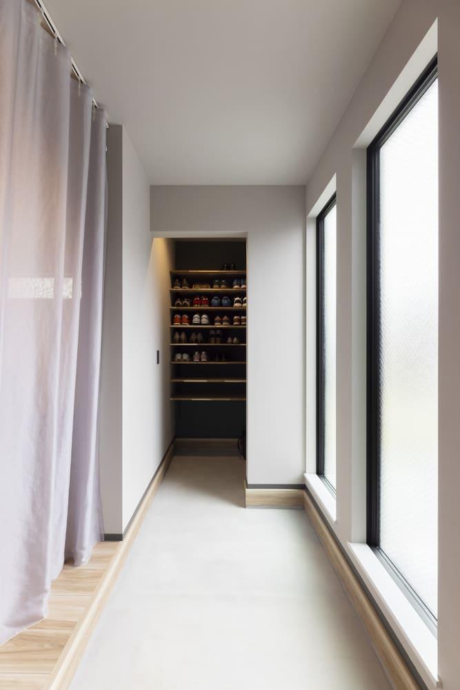 土間スペースはモルタルで仕上げ、内観全体の統一感を高めている。奥には収納に困らないシューズクロークを設置