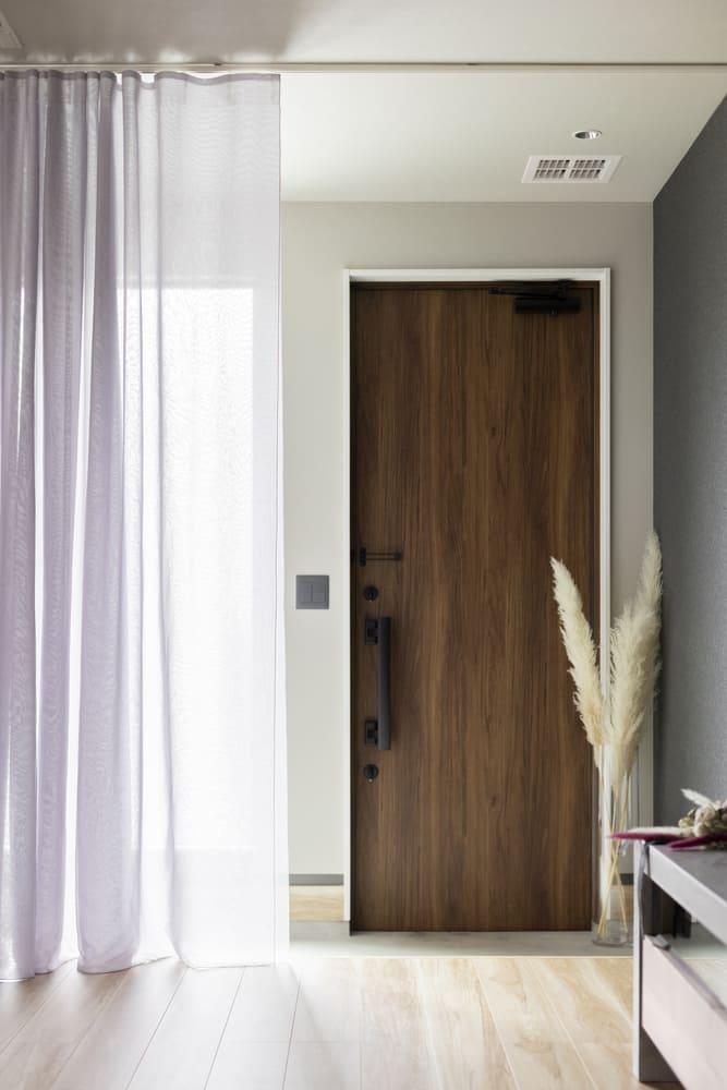 玄関とリビングの間に扉がなく、間仕切りとしてレースのカーテンを用い、空間を柔らかく仕切っている