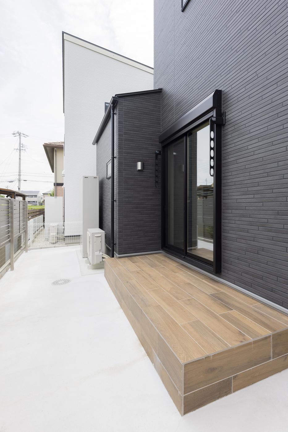 キッチンから繋がる反対側のお庭スペース。木目調のタイルデッキがアクセントに。