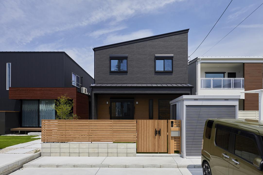 石目調チャコールの外壁をメインに木目調ブラウンのアクセントを採用したスタイリッシュな外観。