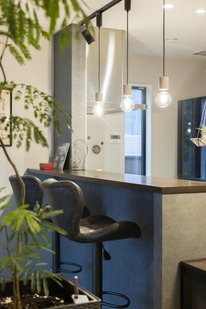 キッチンと対面したバーカウンター。ペンダントライトやカウンターチェアがおしゃれな空間をつくりだしている