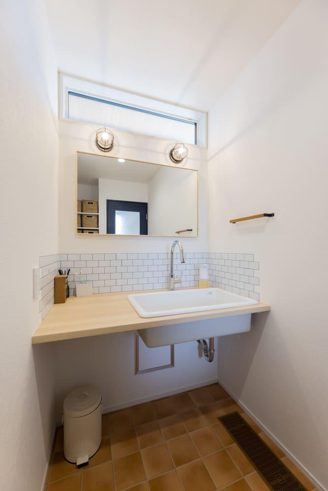 オレンジの床に映えるテラコッタ調の造作洗面台をあしらえた。マリンランプを設置し爽やかな印象に