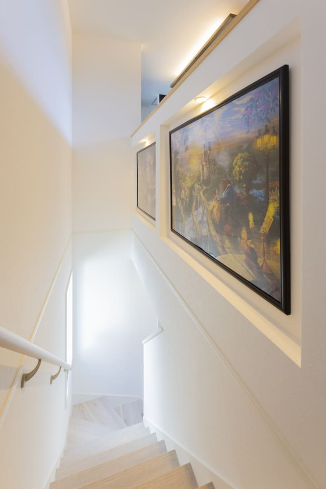 階段の壁面にニッチを施工し、絵画を飾った。寂しくなりがちな階段も華やかな仕上がりに