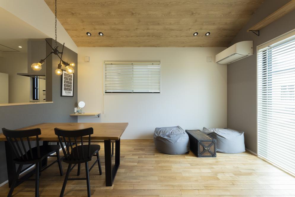 床材は木の導管に黒の塗装が入った無垢材を採用。カッコいい雰囲気のリビング空間に。