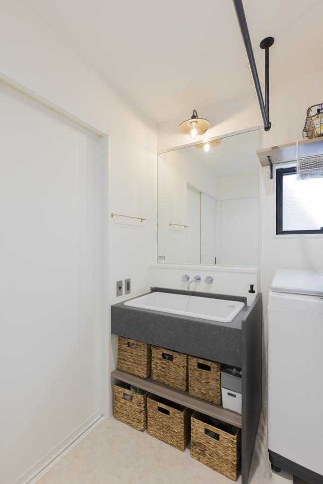 大きなシンクと壁付の水栓、マットグレーのカウンターで設えた造作洗面台。コンセントも新金属のプレートとし雰囲気を統一した。