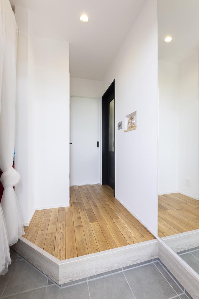 玄関の壁面に大きな鏡を設置。コンパクトながらも広々した空間を感じられる。
