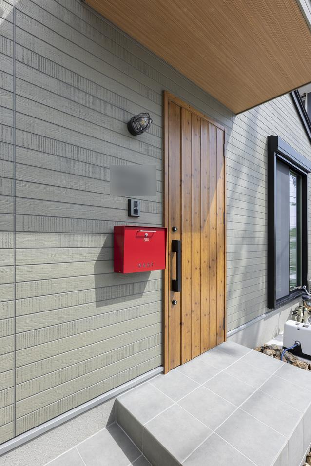 グリーンの外壁に赤いポストが印象的な外観。