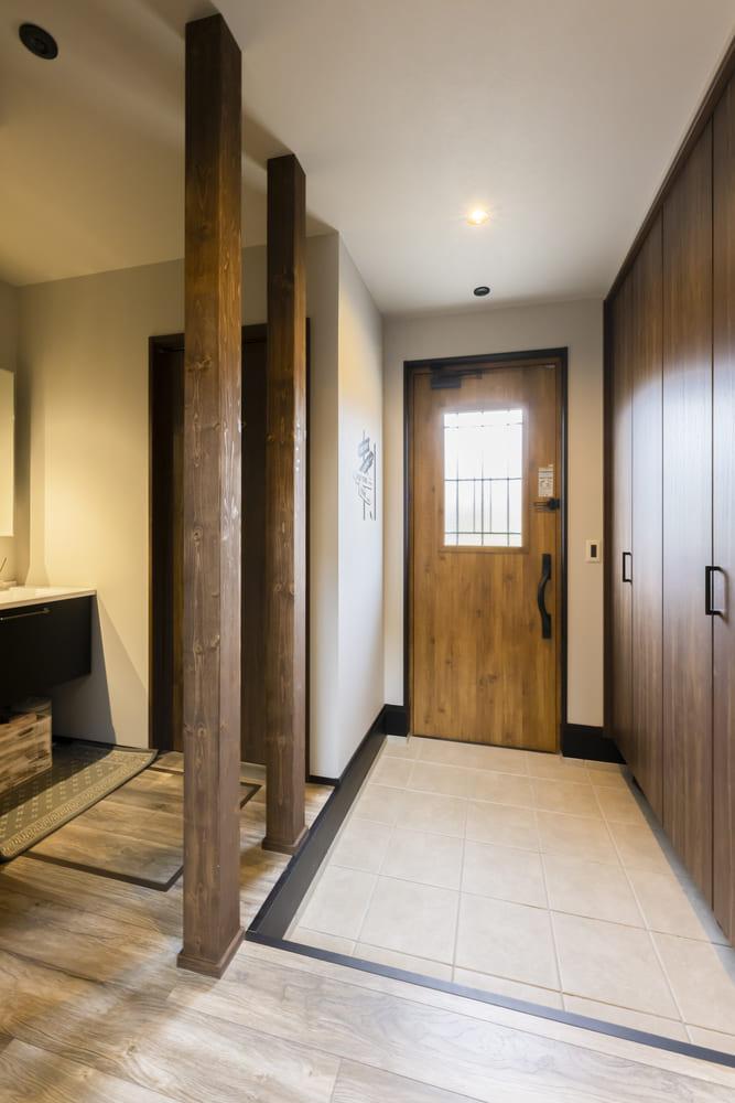 木の質感を生かした温かみのある玄関。オイル塗装を施した化粧柱が緩やかに空間を仕切っている