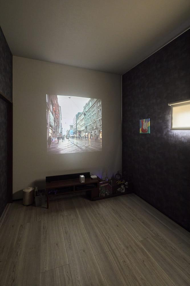 階段の途中で繋がる中二階寝室。3面にダークトーンのアクセントクロスを施し、正面壁にはプロジェクターを大胆に映し出すことができる贅沢なお部屋に仕上がった